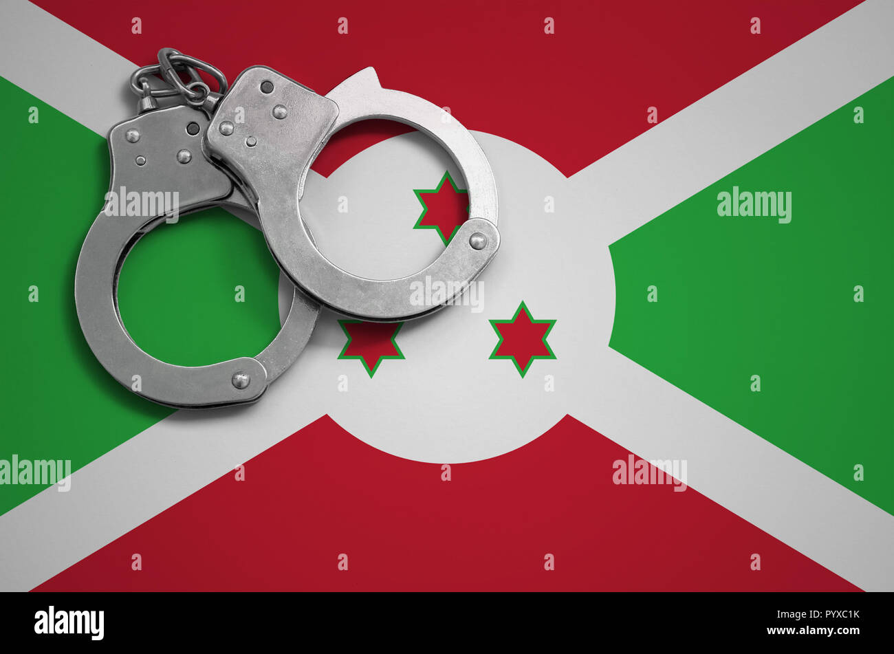 Burundi flag  and police handcuffs. The concept of crime and offenses in the country. - Stock Image