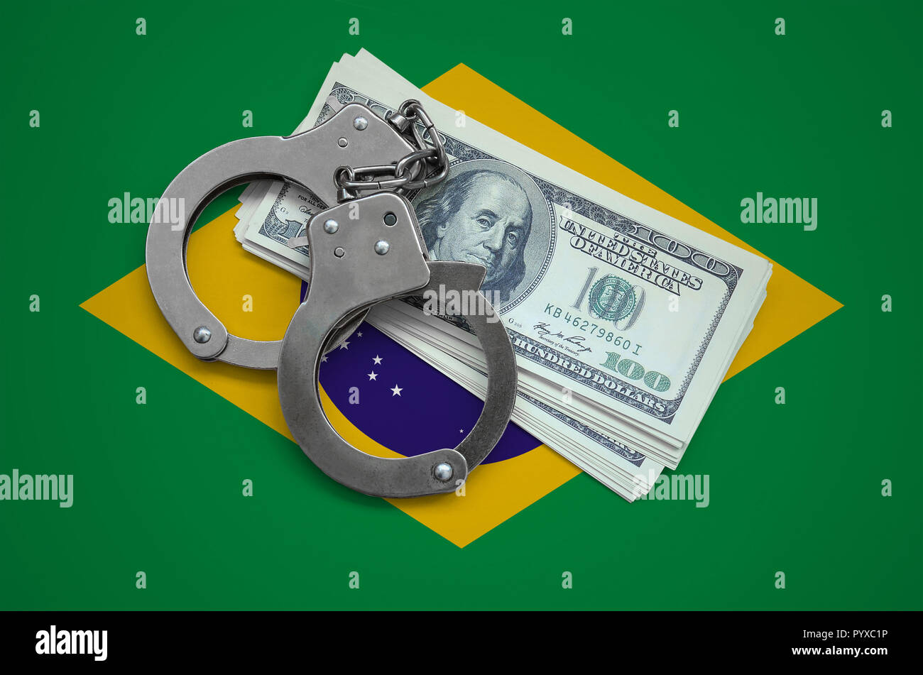 Brazil flag  with handcuffs and a bundle of dollars. Currency corruption in the country. Financial crimes. - Stock Image