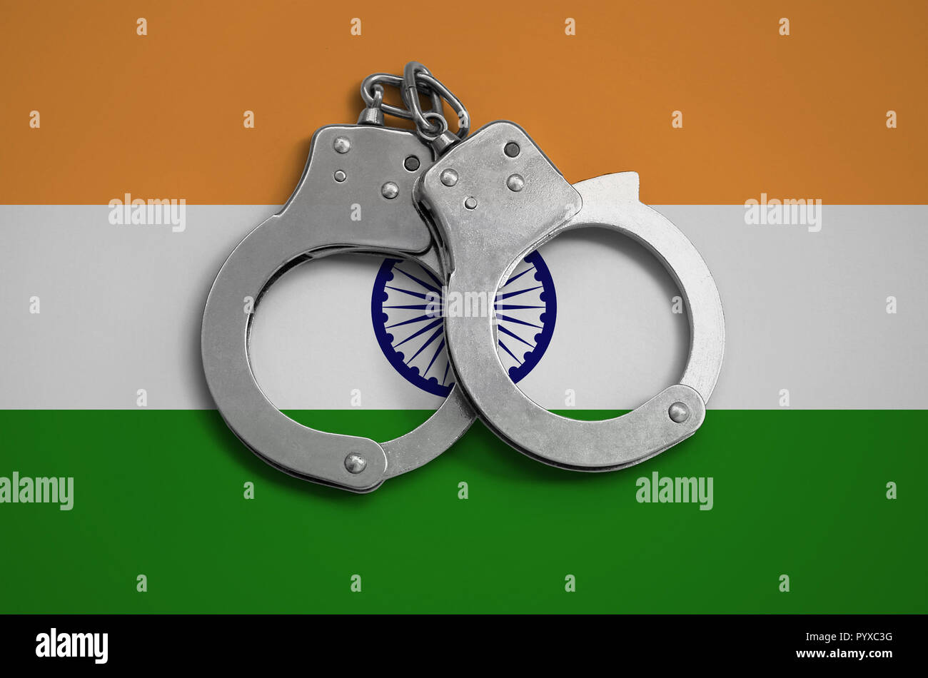 India flag  and police handcuffs. The concept of observance of the law in the country and protection from crime. - Stock Image