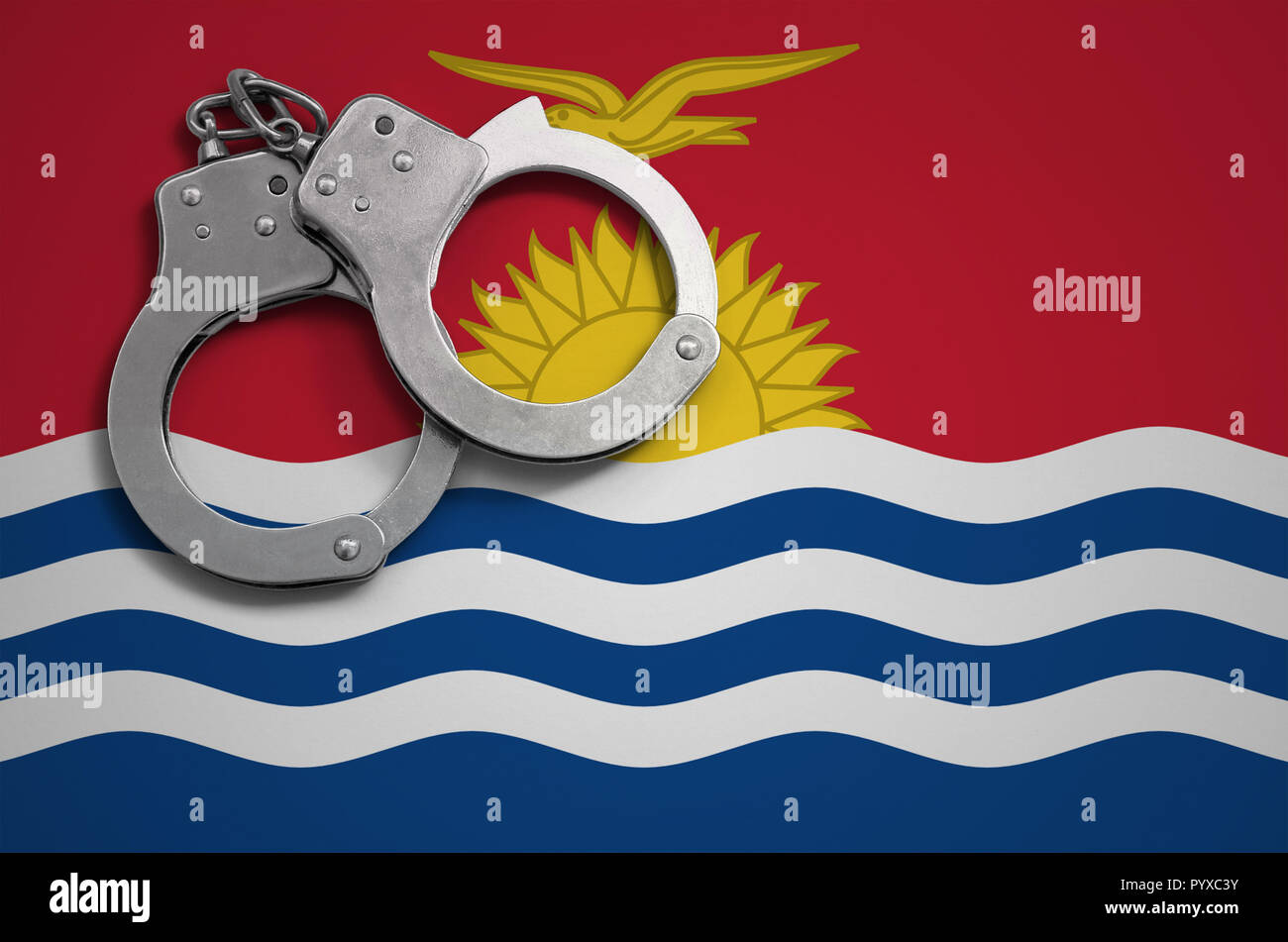 Kiribati flag  and police handcuffs. The concept of crime and offenses in the country. - Stock Image