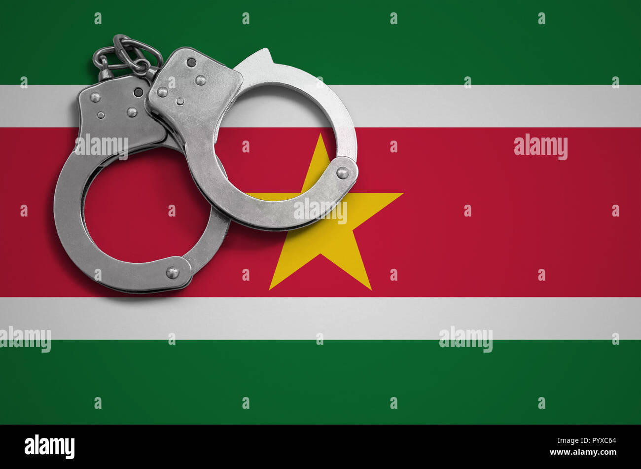 Suriname flag  and police handcuffs. The concept of crime and offenses in the country. - Stock Image