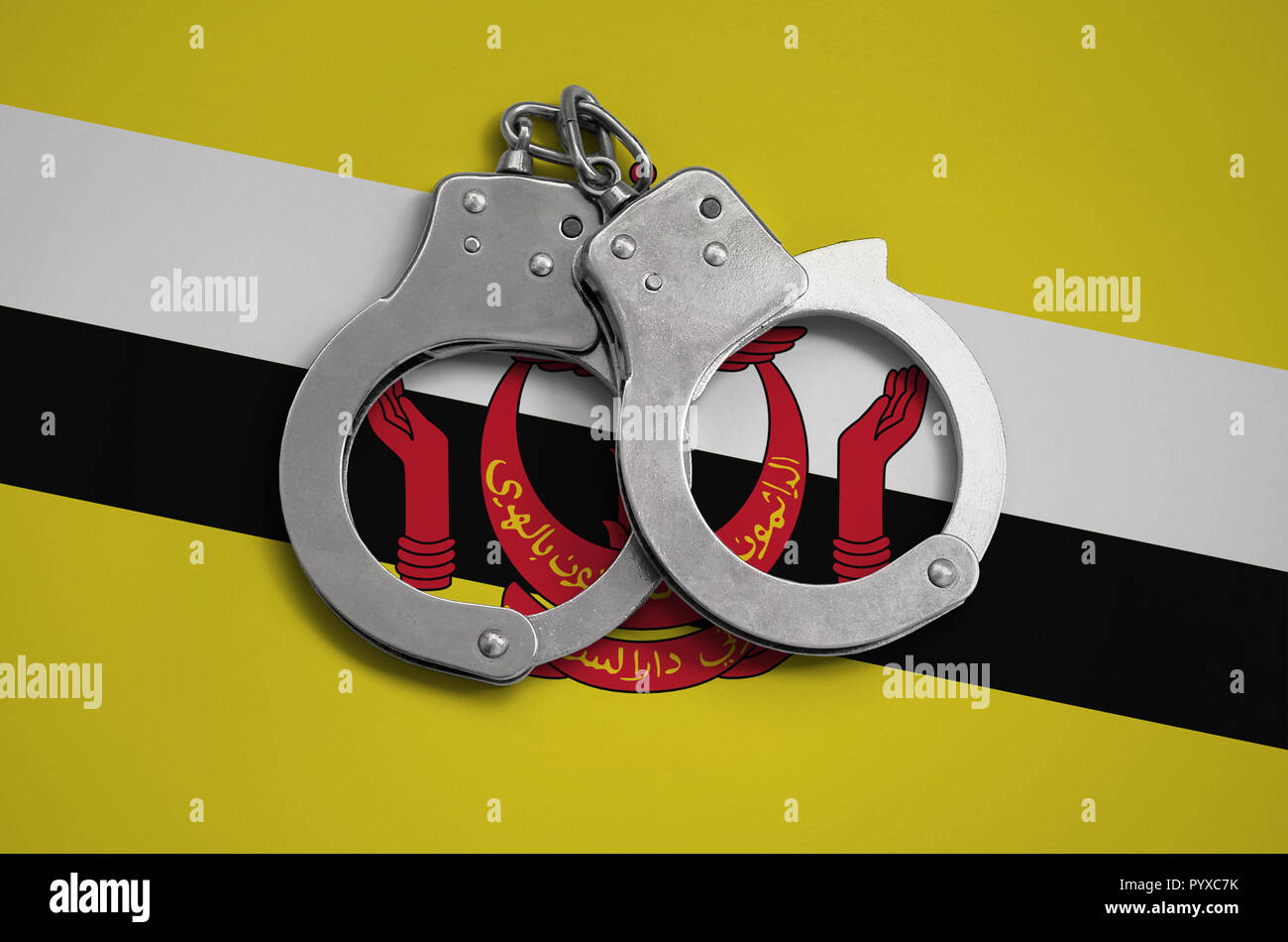 Brunei Darussalam flag  and police handcuffs. The concept of observance of the law in the country and protection from crime. - Stock Image