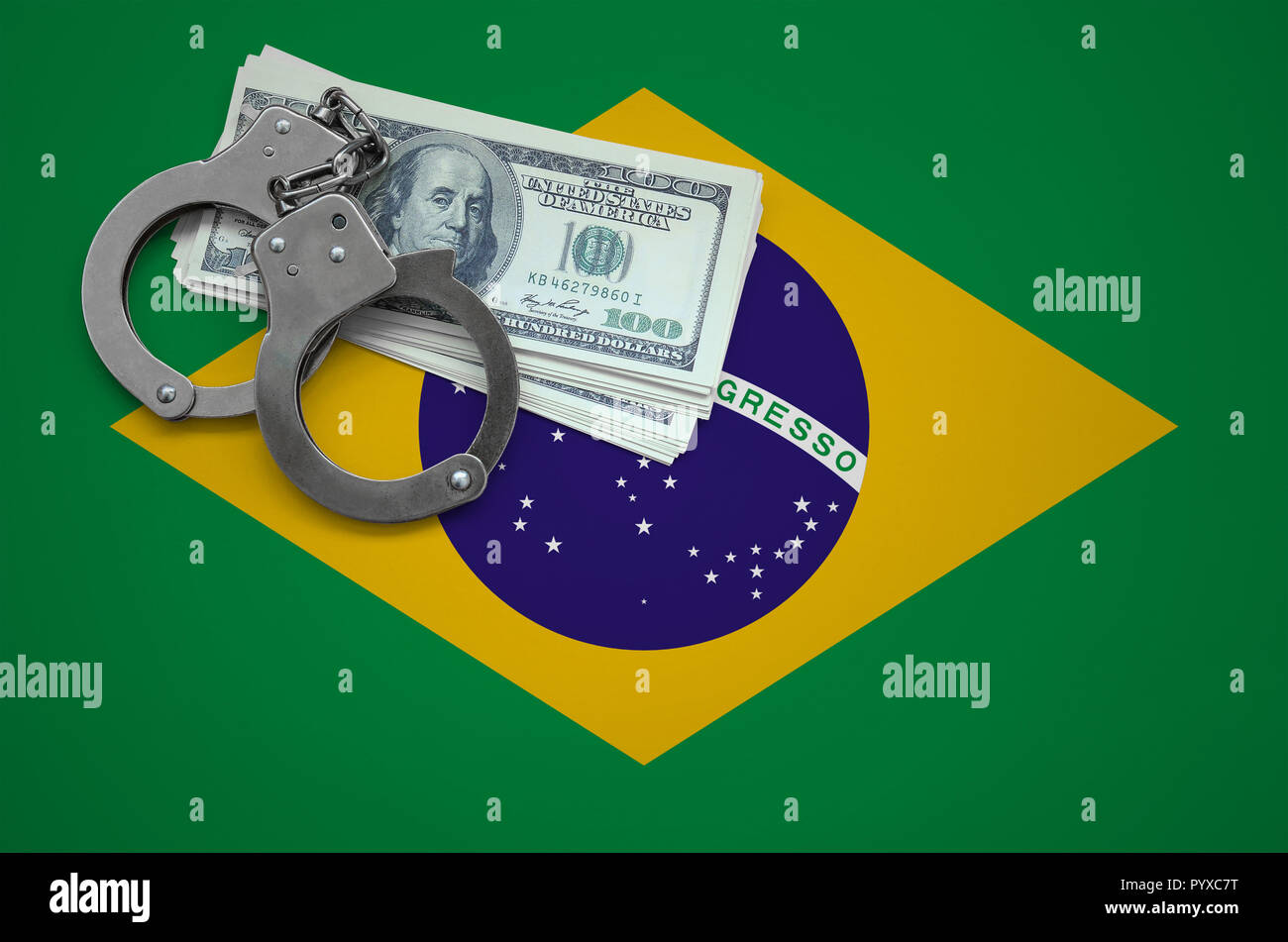 Brazil flag  with handcuffs and a bundle of dollars. The concept of breaking the law and thieves crimes. - Stock Image