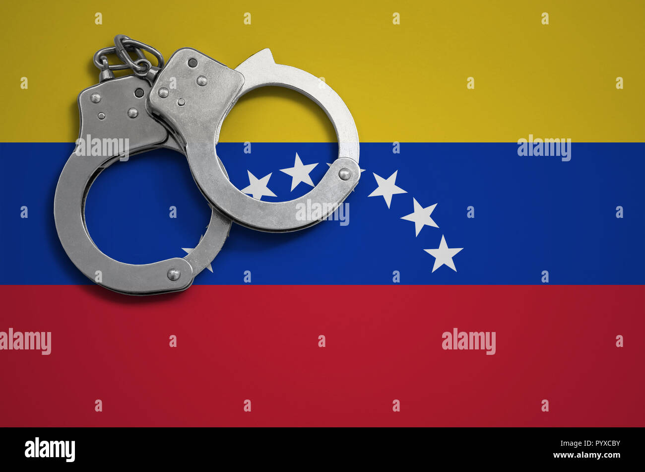 Venezuela flag  and police handcuffs. The concept of crime and offenses in the country. - Stock Image