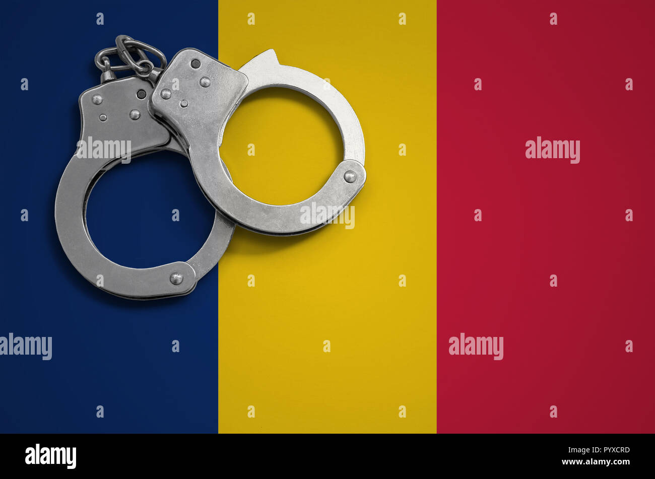 Chad flag  and police handcuffs. The concept of crime and offenses in the country. - Stock Image