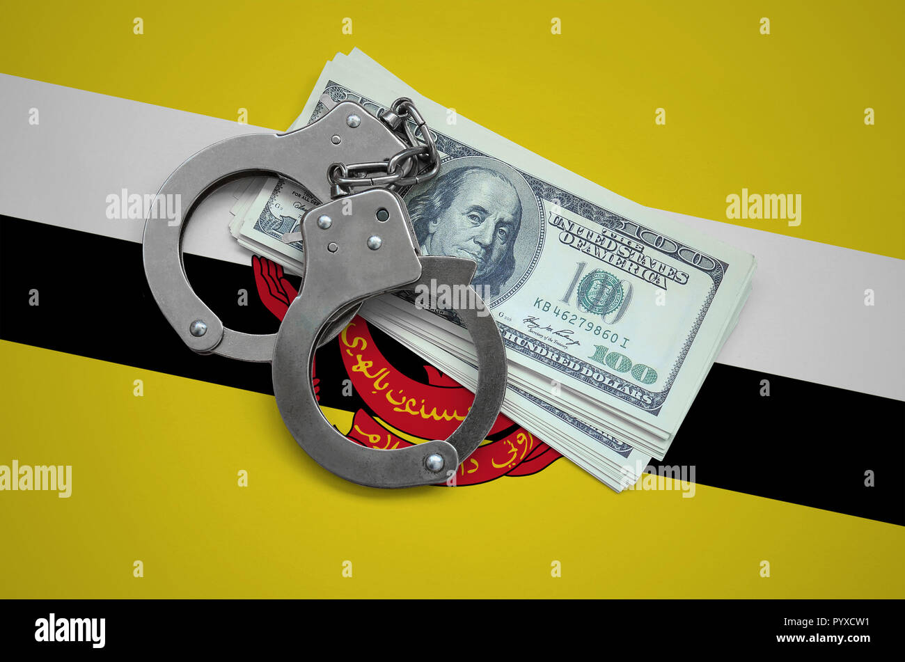 Brunei Darussalam flag  with handcuffs and a bundle of dollars. Currency corruption in the country. Financial crimes. - Stock Image