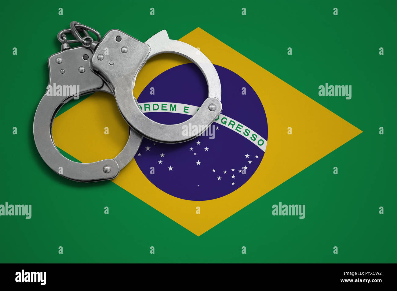 Brazil flag  and police handcuffs. The concept of crime and offenses in the country. - Stock Image
