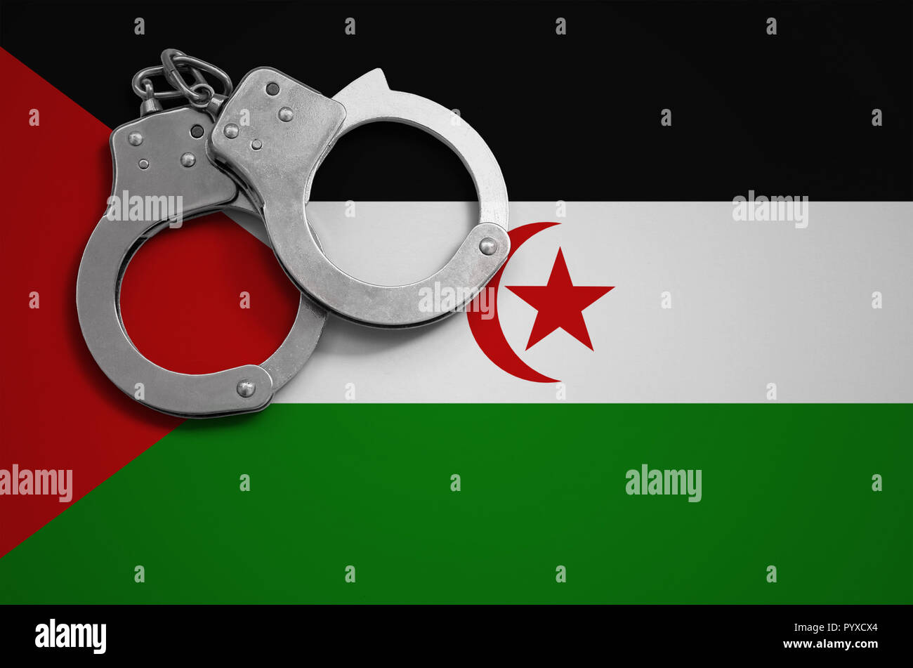 Western Sahara flag  and police handcuffs. The concept of crime and offenses in the country. - Stock Image
