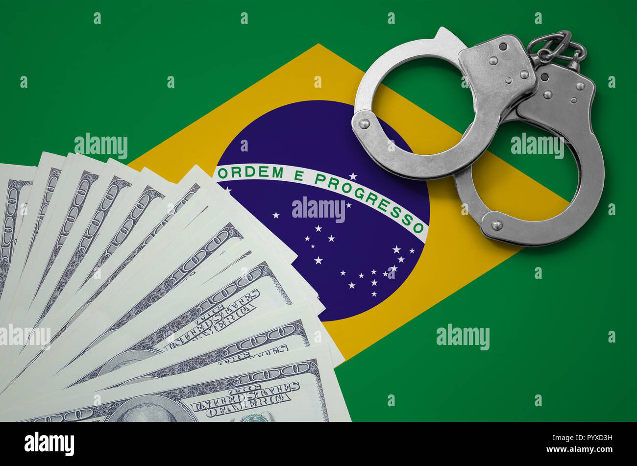 Brazil flag  with handcuffs and a bundle of dollars. The concept of illegal banking operations in US currency. - Stock Image