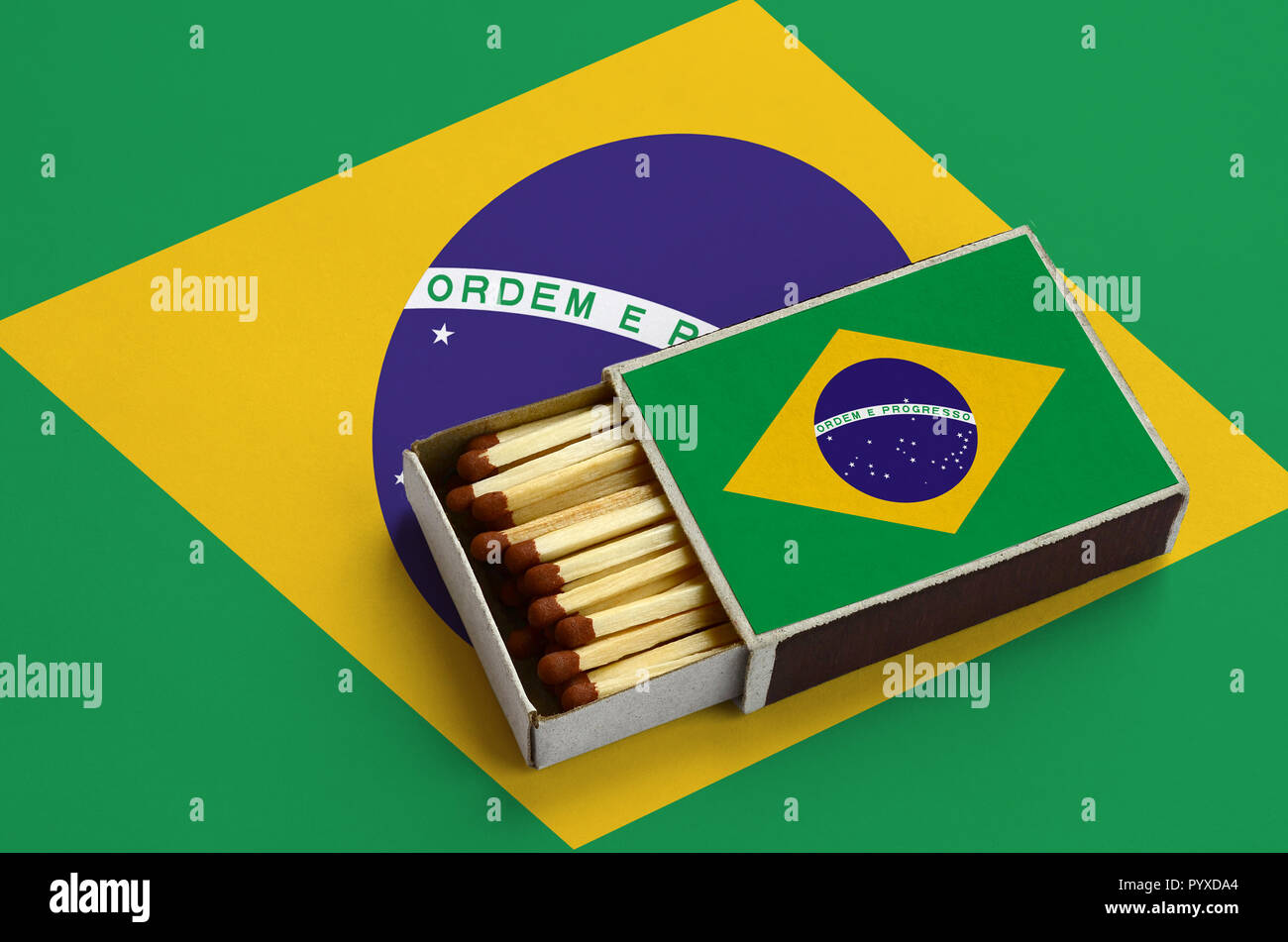 Brazil flag  is shown in an open matchbox, which is filled with matches and lies on a large flag. - Stock Image