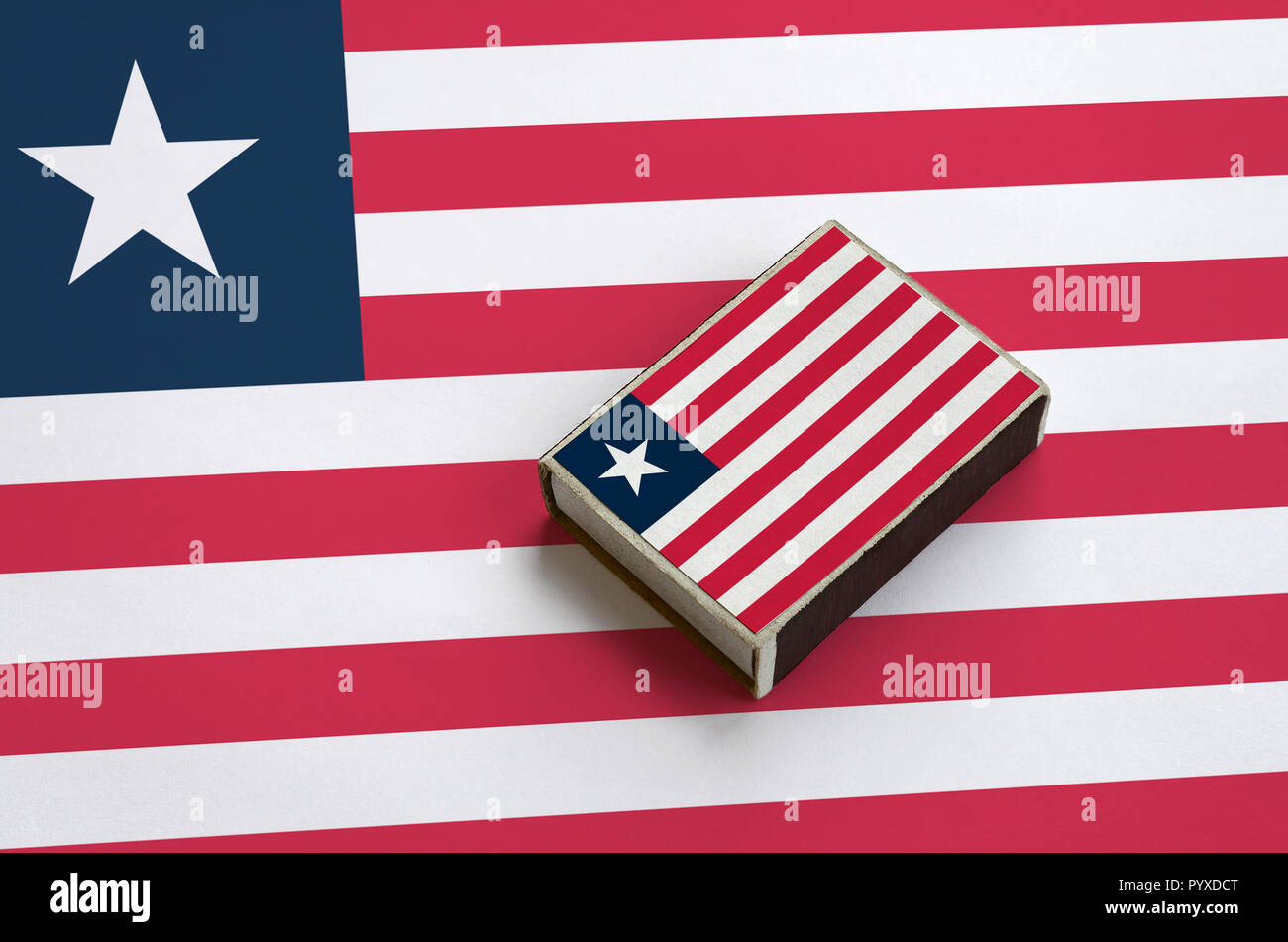 Liberia flag  is pictured on a matchbox that lies on a large flag. - Stock Image