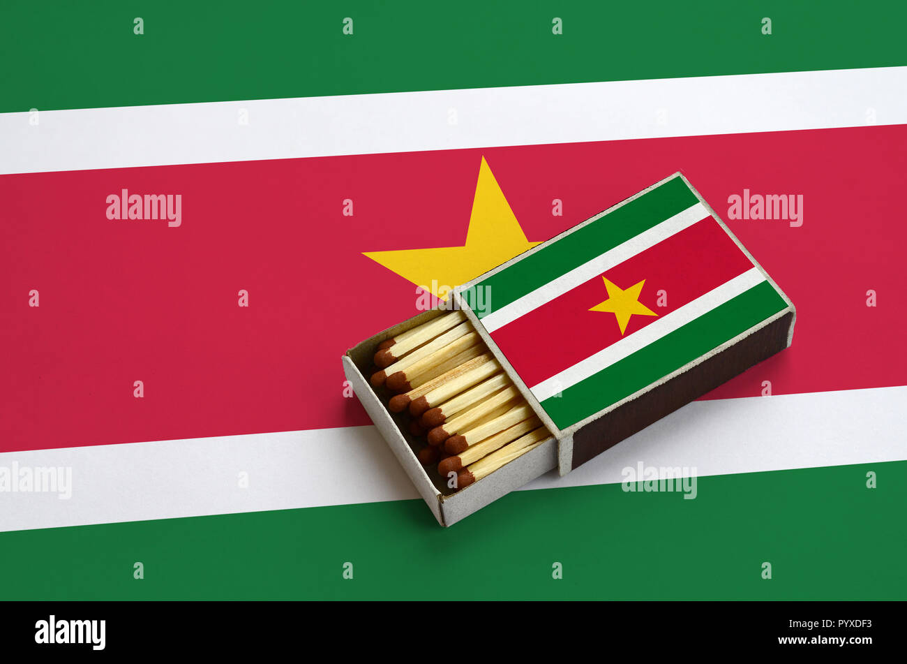 Suriname flag  is shown in an open matchbox, which is filled with matches and lies on a large flag. - Stock Image