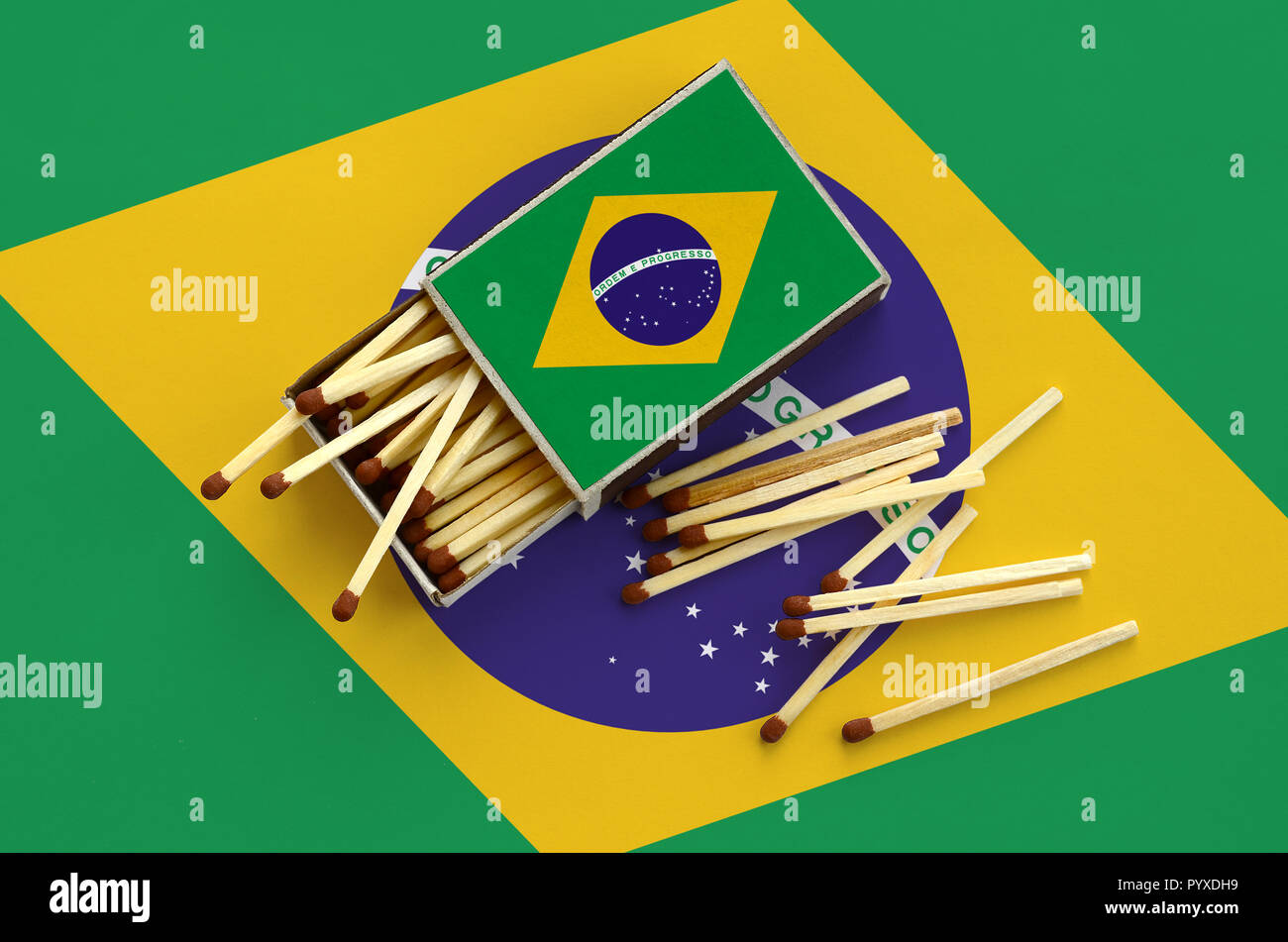 Brazil flag  is shown on an open matchbox, from which several matches fall and lies on a large flag. - Stock Image