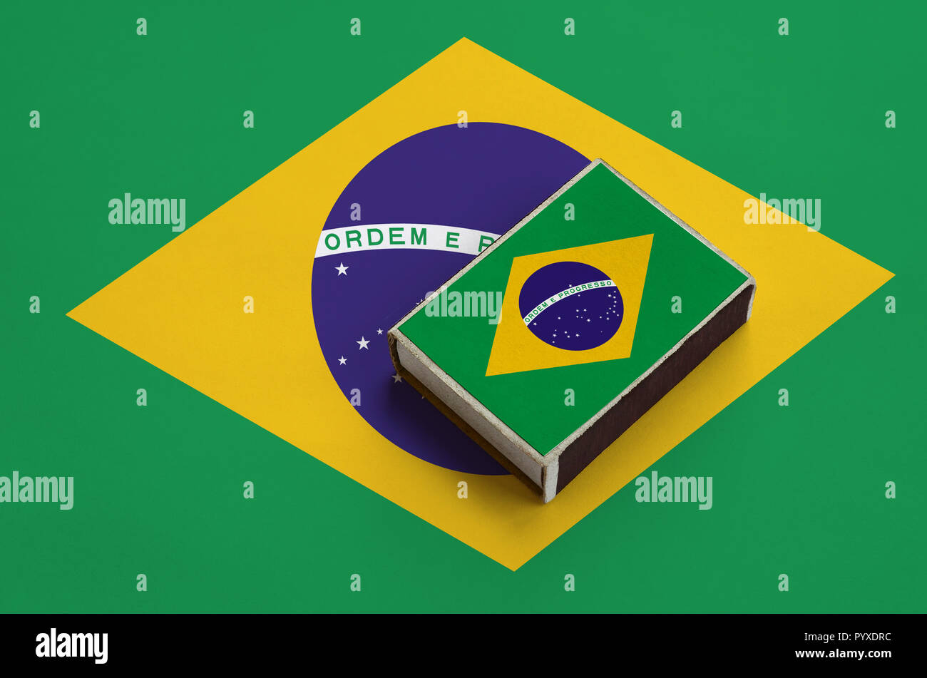 Brazil flag  is pictured on a matchbox that lies on a large flag. - Stock Image