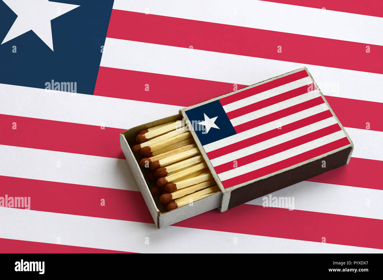 Liberia flag  is shown in an open matchbox, which is filled with matches and lies on a large flag. - Stock Image