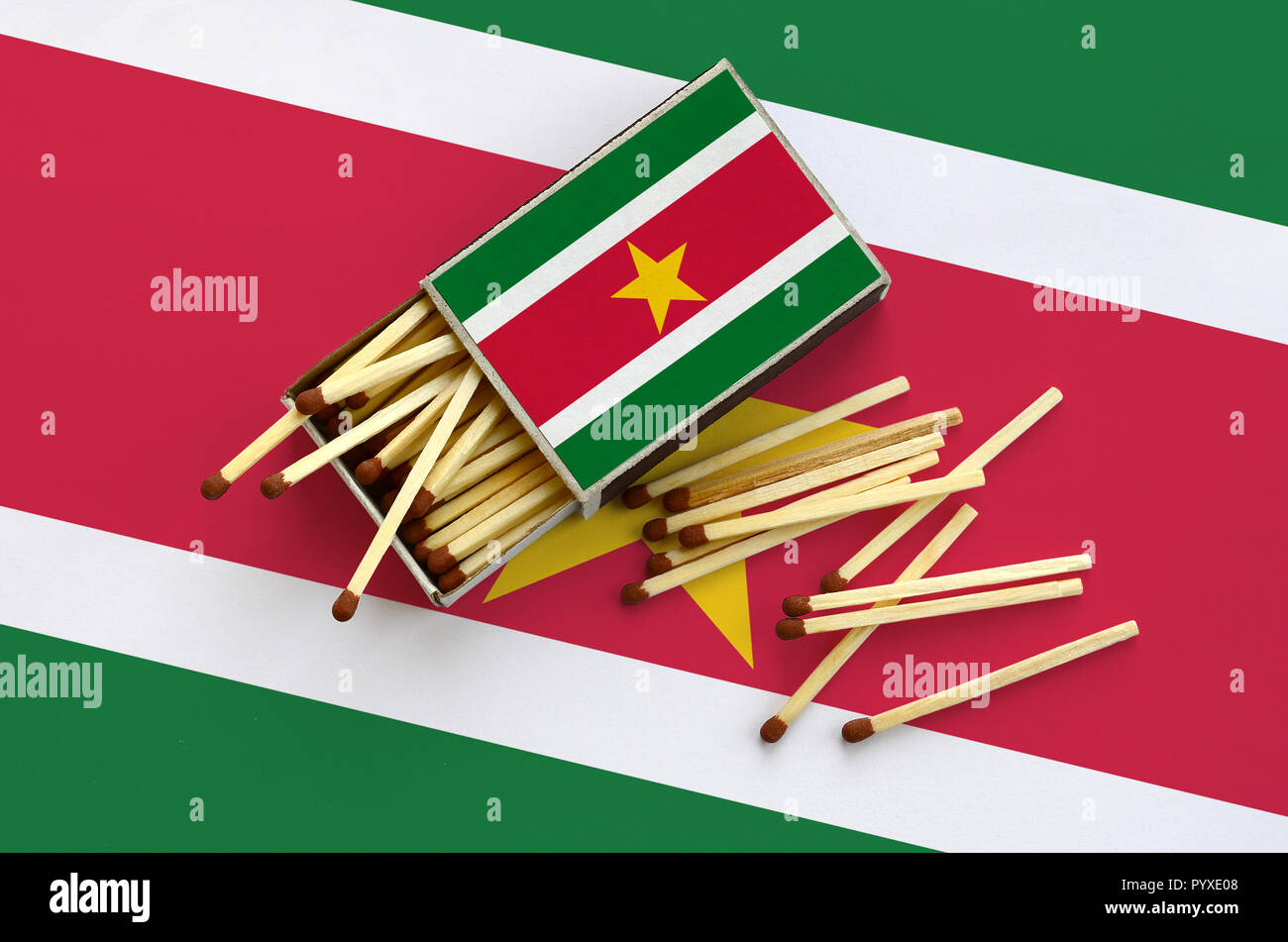 Suriname flag  is shown on an open matchbox, from which several matches fall and lies on a large flag. - Stock Image