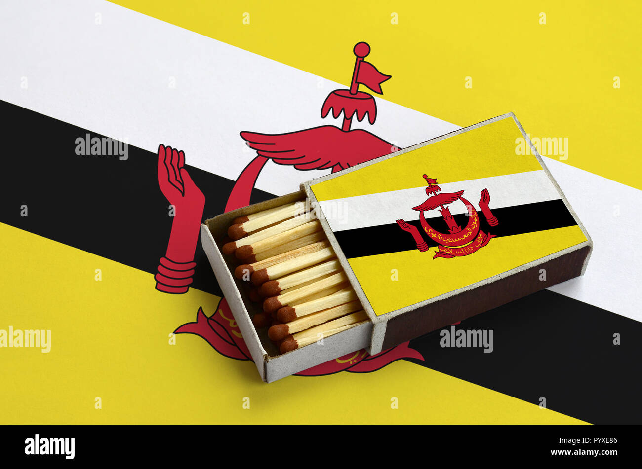 Brunei Darussalam flag  is shown in an open matchbox, which is filled with matches and lies on a large flag. - Stock Image