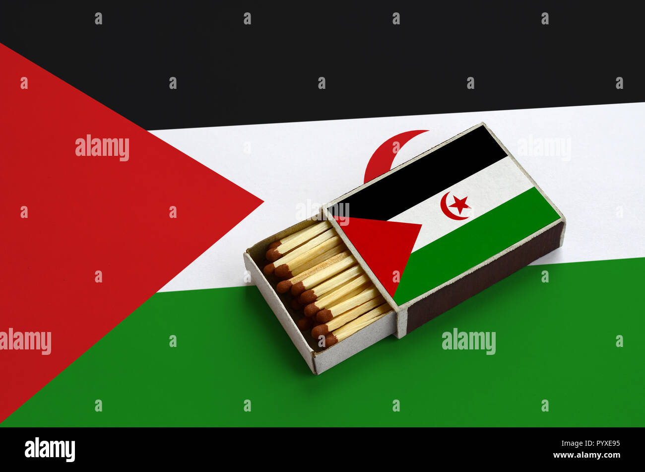 Western Sahara flag  is shown in an open matchbox, which is filled with matches and lies on a large flag. Stock Photo