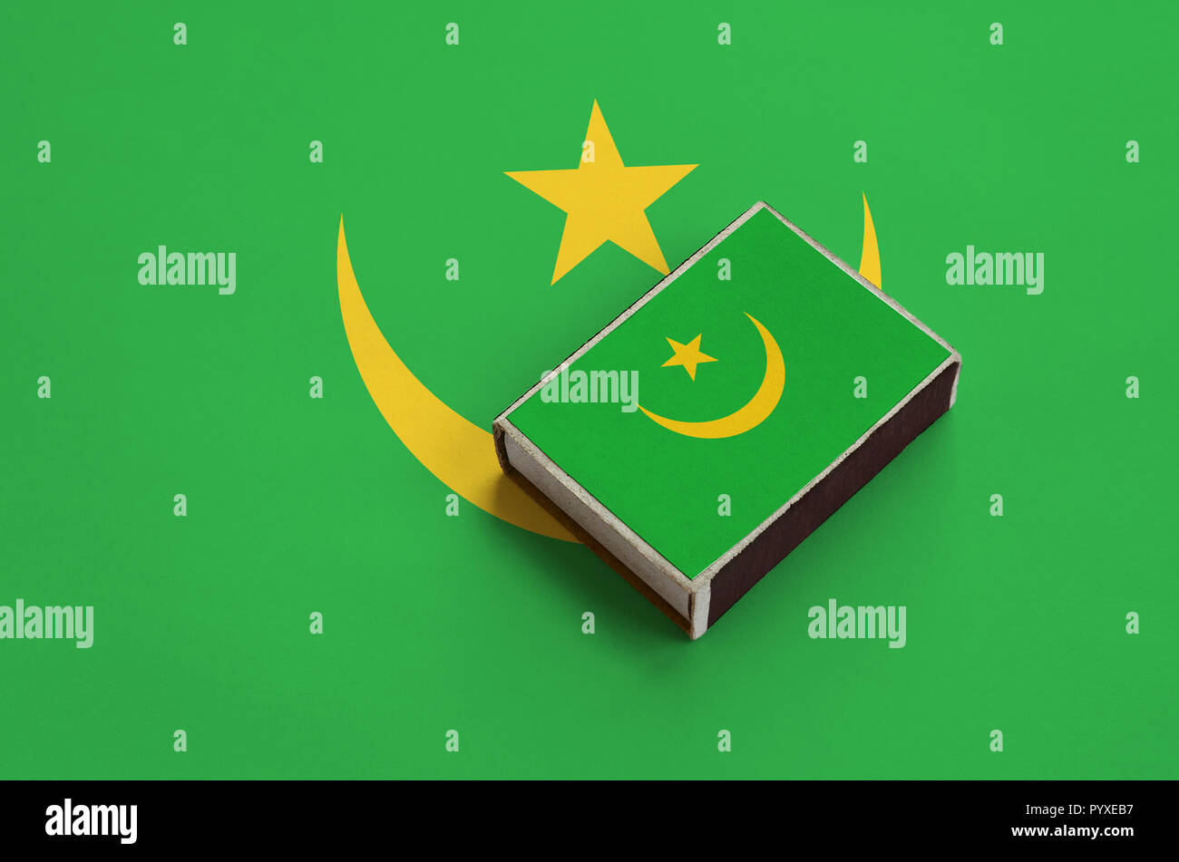 Mauritania flag  is pictured on a matchbox that lies on a large flag. - Stock Image