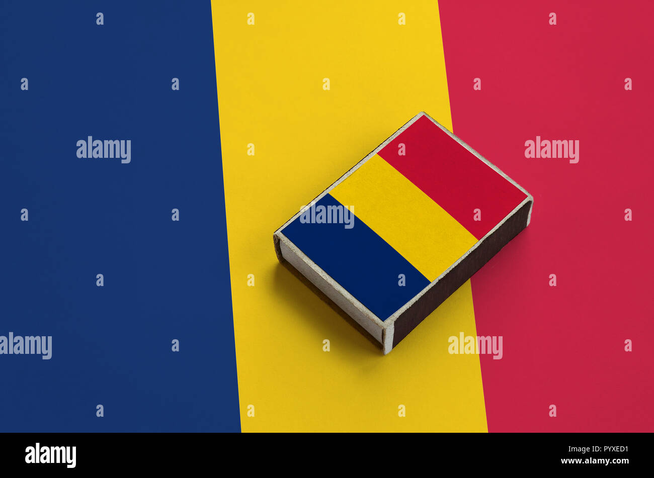 Chad flag  is pictured on a matchbox that lies on a large flag. - Stock Image