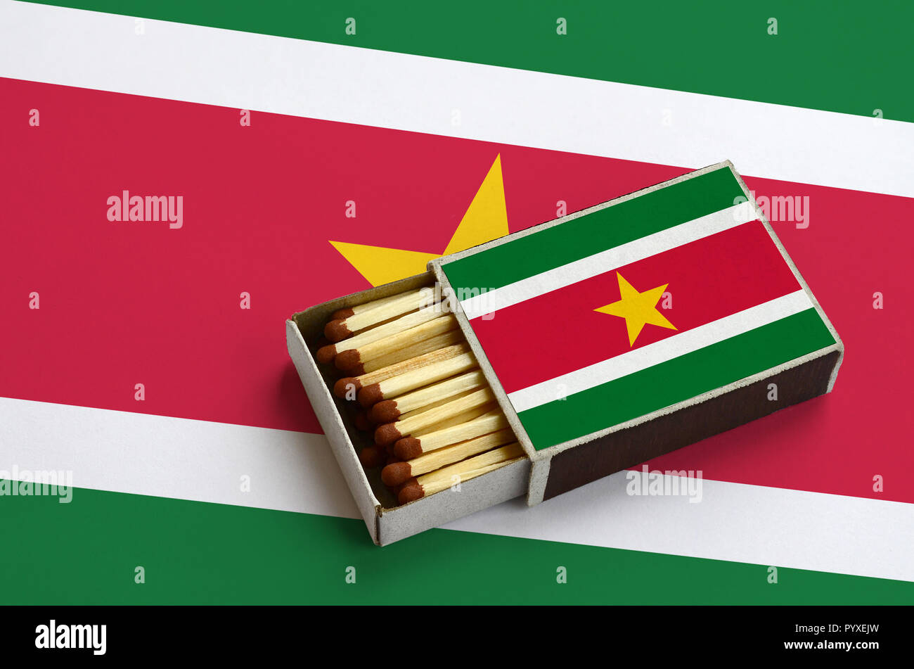 Suriname flag  is shown in an open matchbox, which is filled with matches and lies on a large flag. Stock Photo