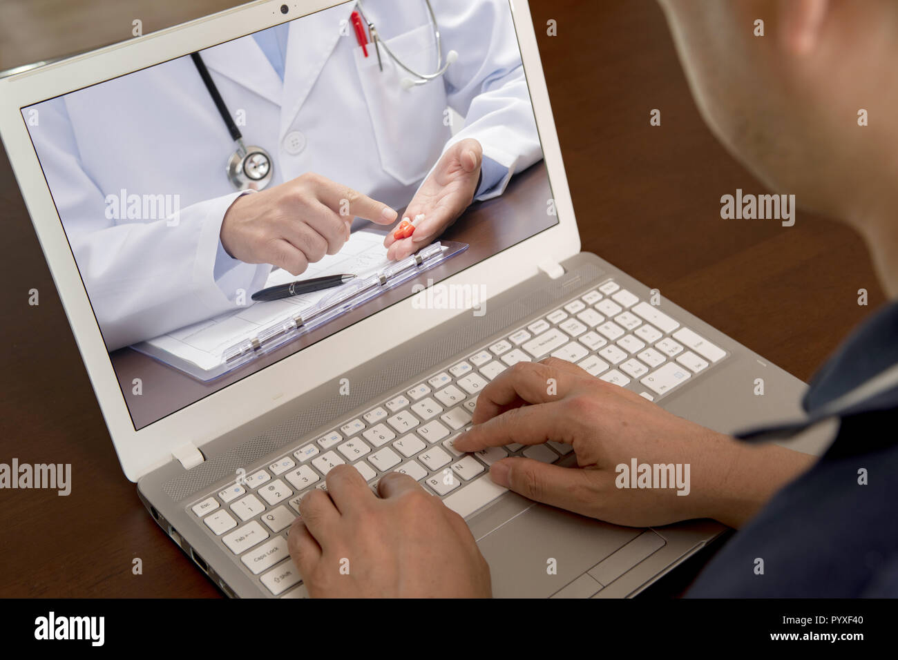 A middle-aged man who uses telemedicine to listen to a doctor for medication. - Stock Image
