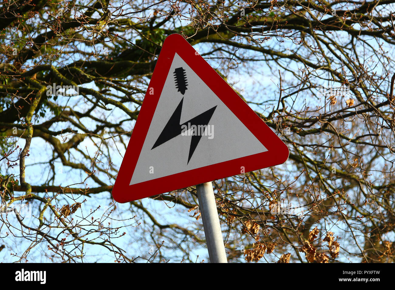 A triangular road sign warning of overhead electric power lines, England, UK - Stock Image