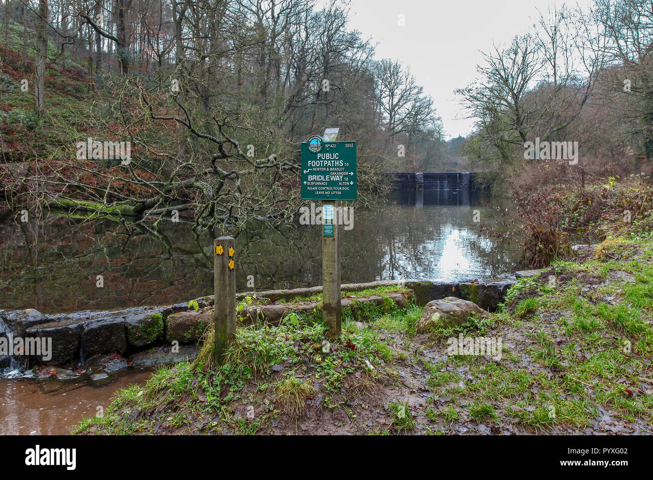 A metal footpath sign erected by Peak and Northern Footpaths Society at the fish ponds, Dimmingsdale, near to Oakamoor, Staffordshire, England, UK - Stock Image