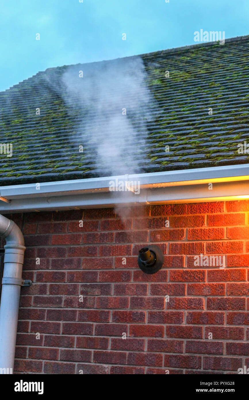 A gas central heating vent on a cold winter evening with plenty of exhaust fumes and steam coming out, Stoke-on-Trent, Staffordshire, England, UK - Stock Image