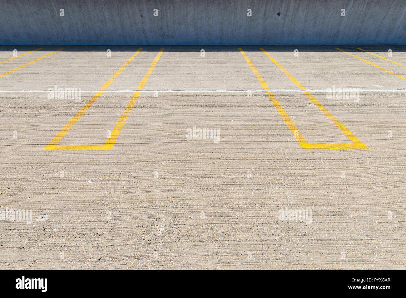 Empty parking spaces with yellow lines in a parking garage. Stock Photo