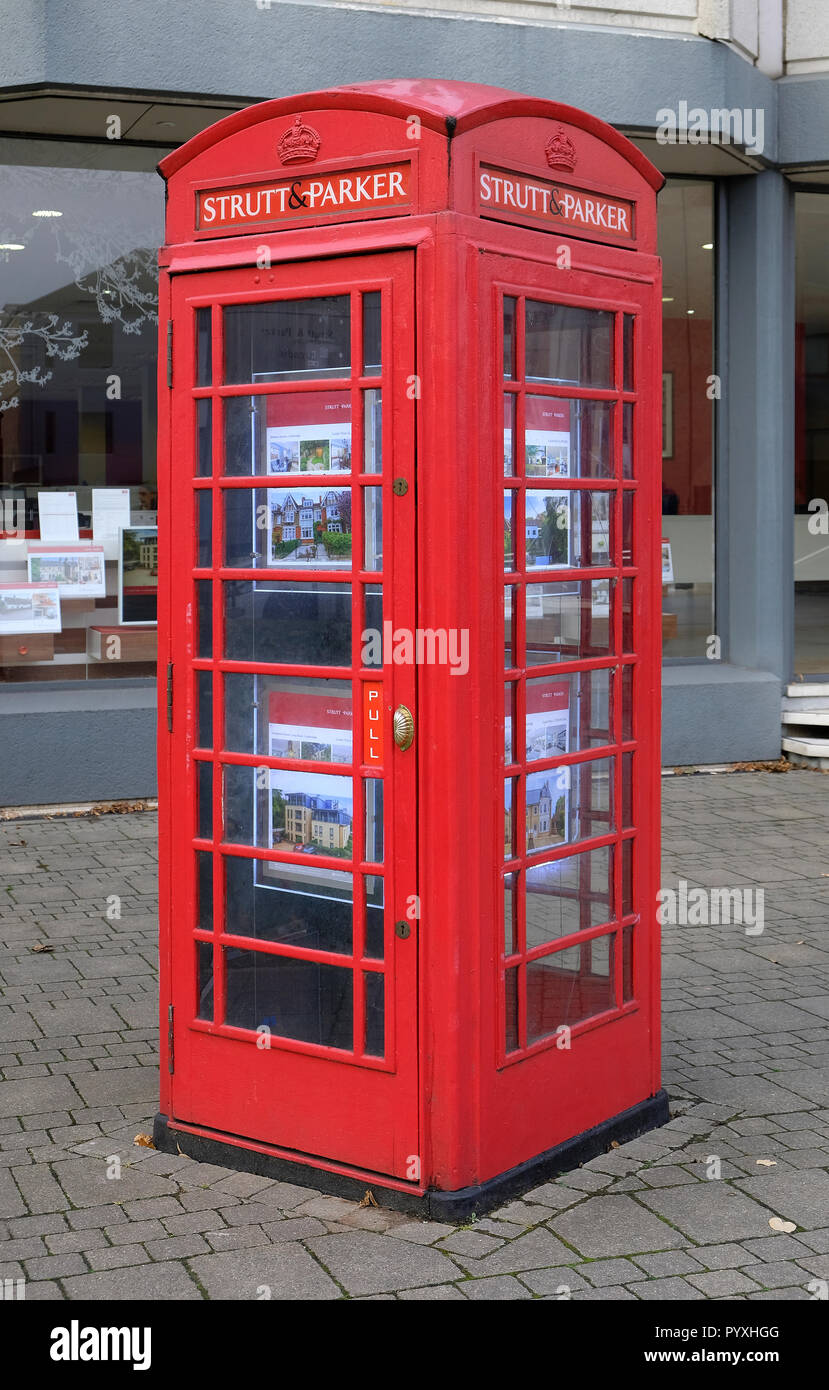 novelty british red telephone box used as estate agents display - Stock Image