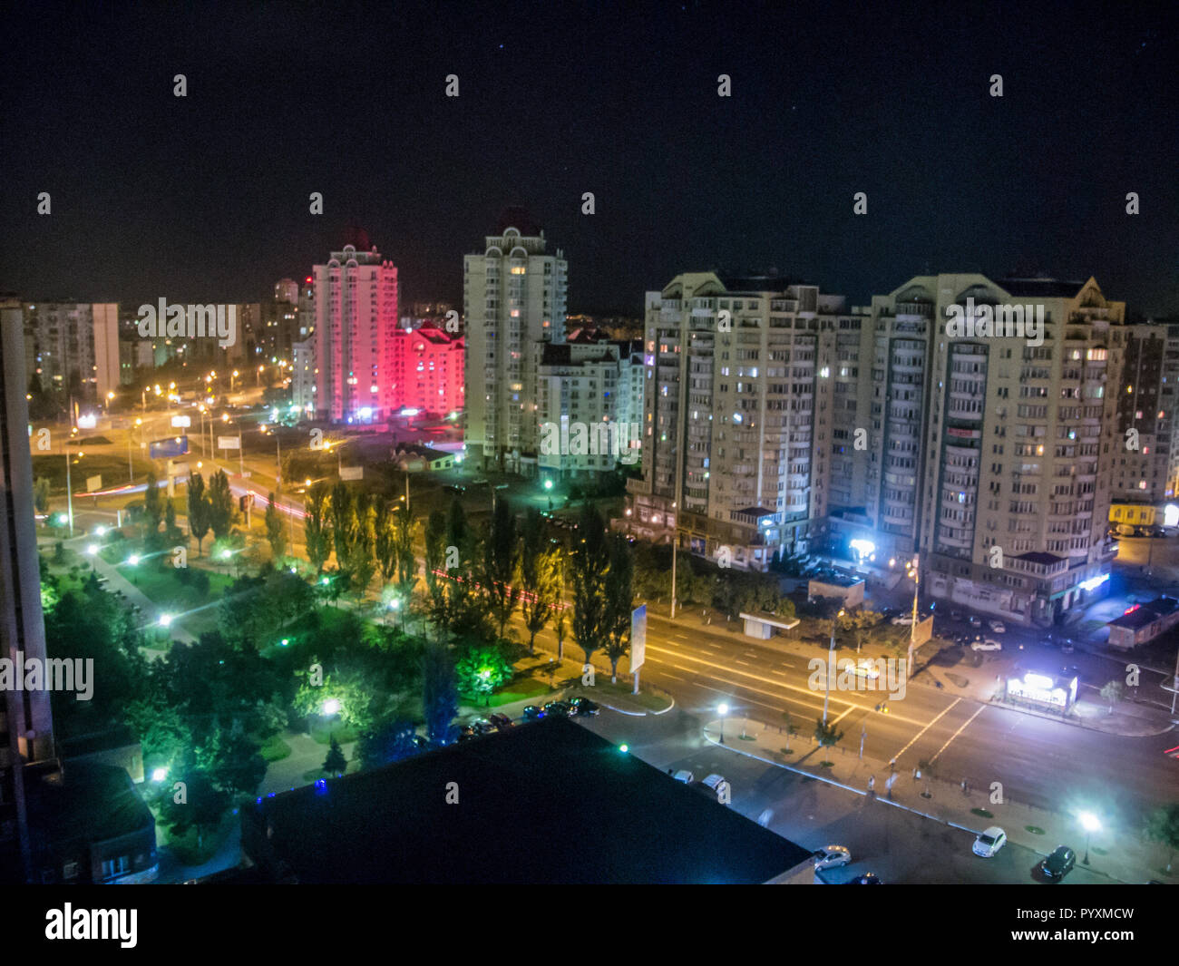 Night city landscape, sleeping quarters with tall houses and crossroads - Stock Image