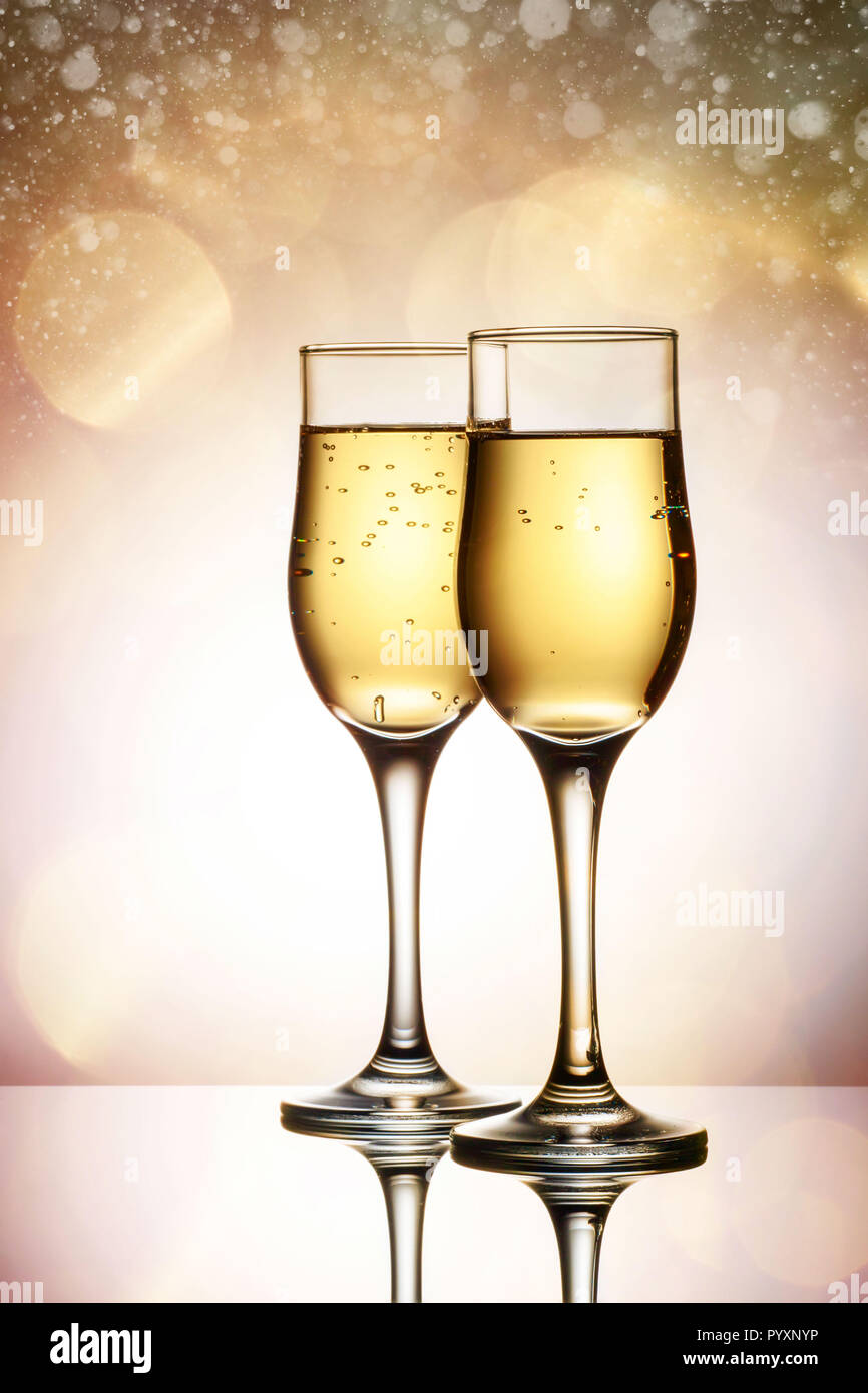 two elegant glasses with sparkling champagne holiday card christmas new year wedding celebration concept with effects of selective focus on bokeh