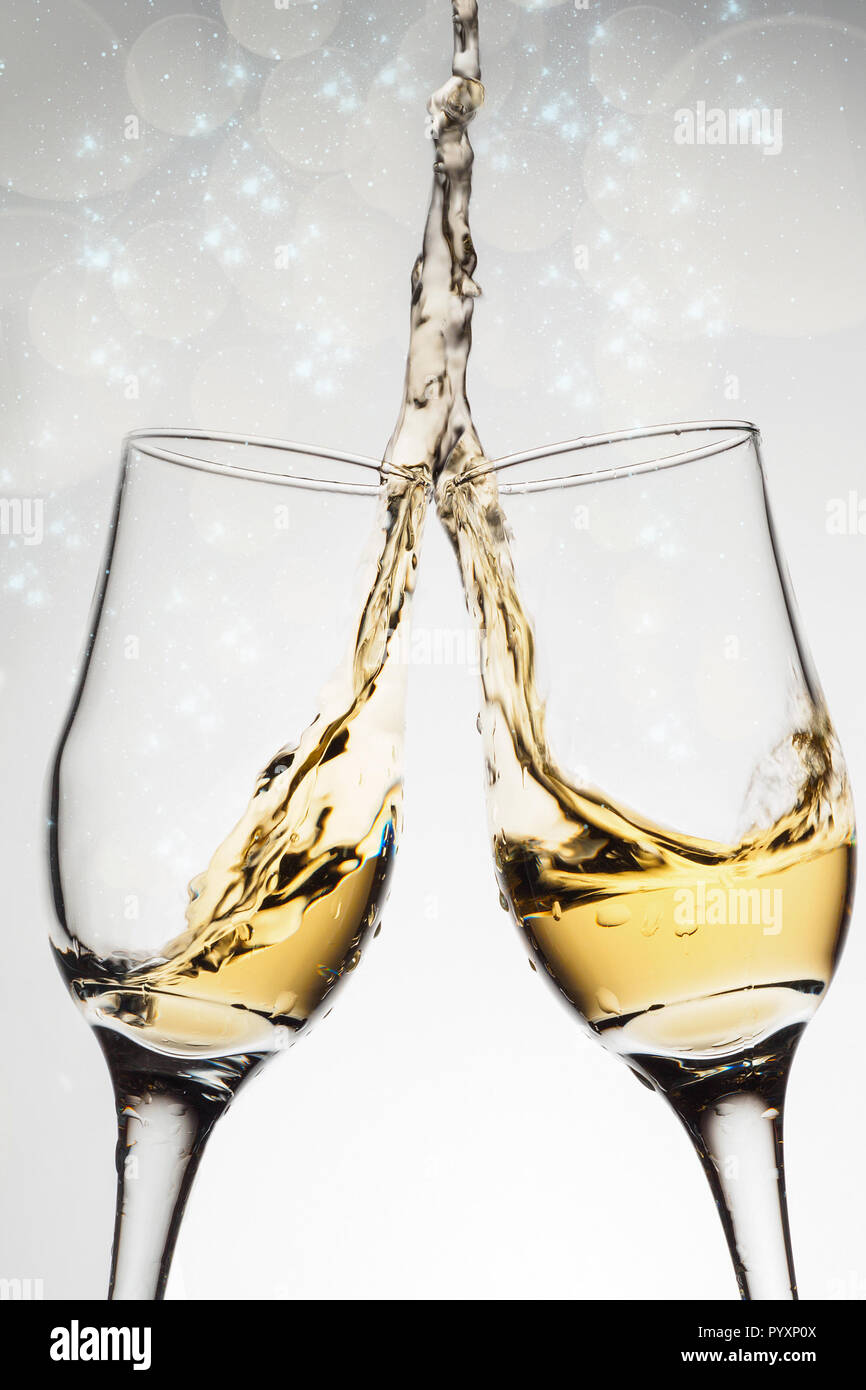 two elegant glasses with sparkling champagne with splash holiday card christmas new year wedding celebration concept with effects of selective foc