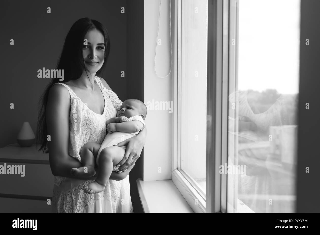 Black And White Shot Of Beautiful Young Mother Carrying Baby Near Window At Home And Looking At Camera Stock Photo Alamy
