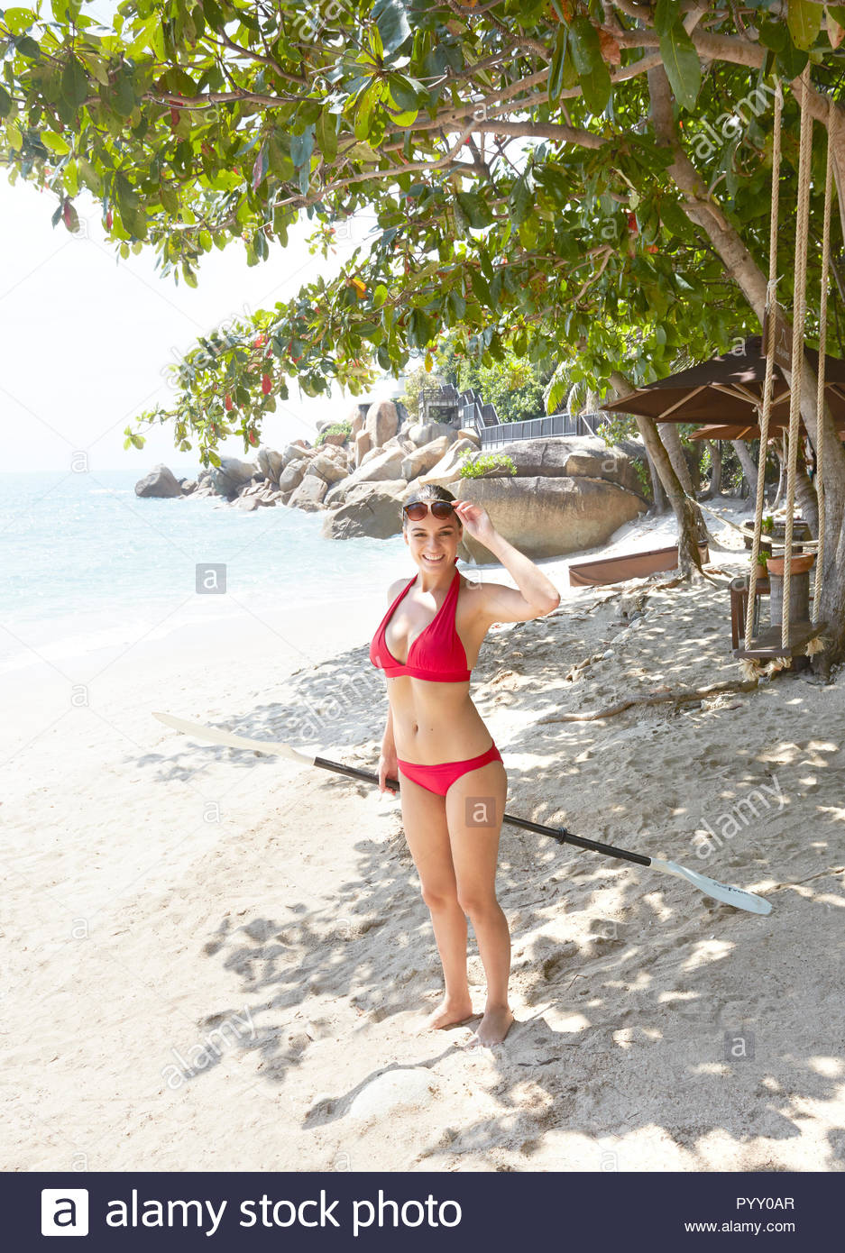 Young woman wearing red bikini holding oar on beach - Stock Image