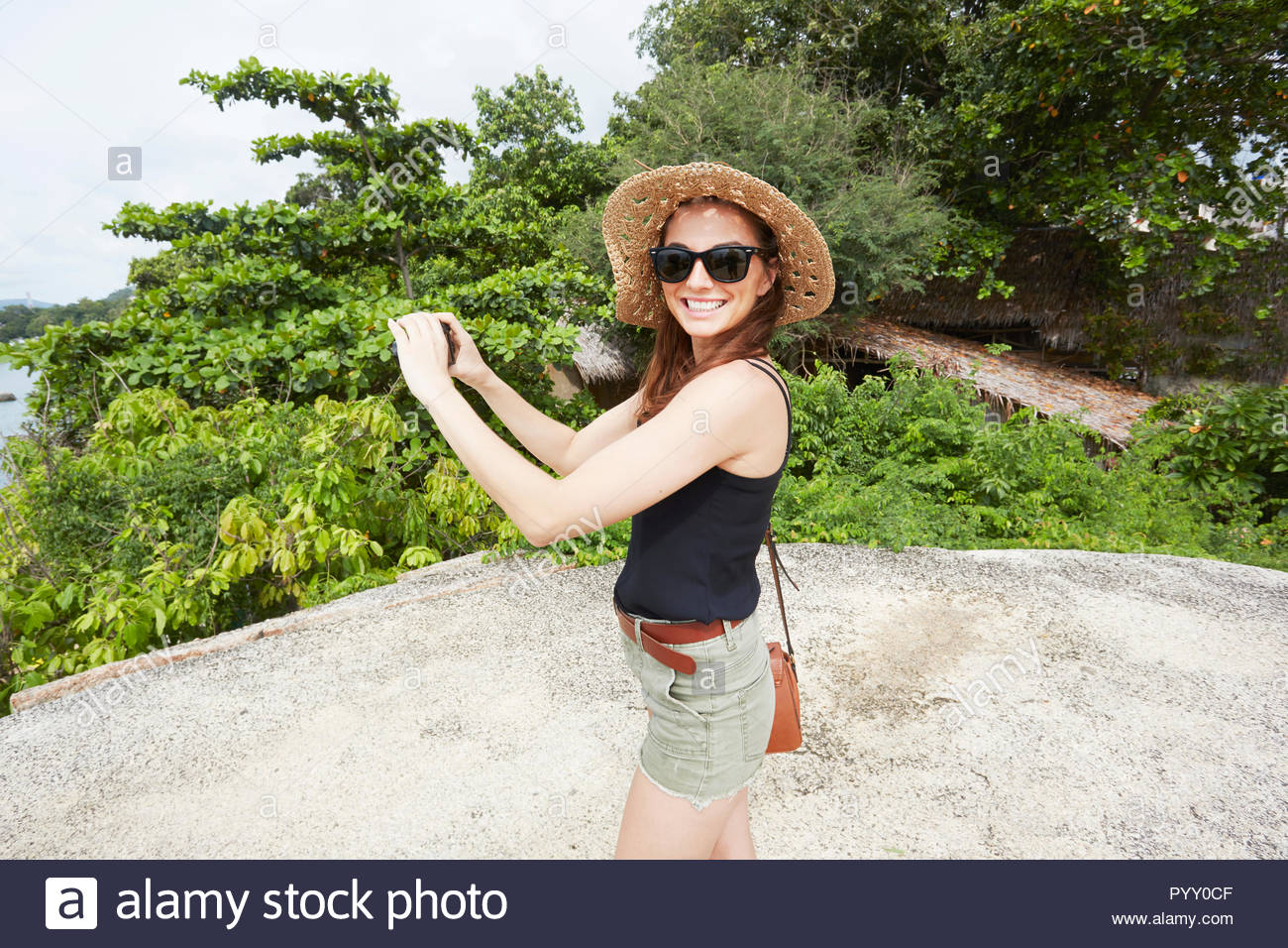 Young woman wearing sunglasses holding camera on rock Stock Photo