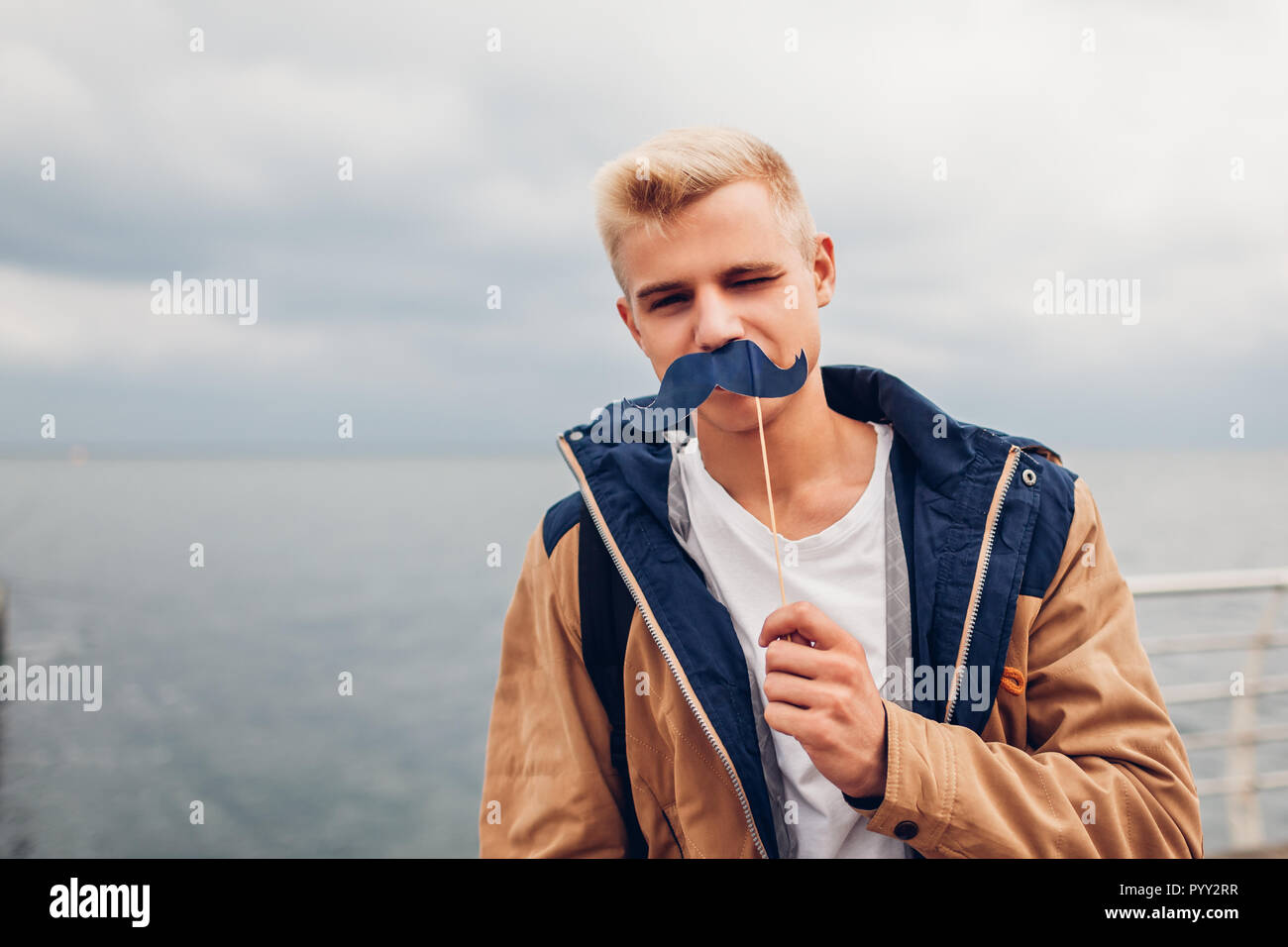 happy college student with backpack holding photo booth props moustache by sea. Guy having fun outdoors. Man winking - Stock Image