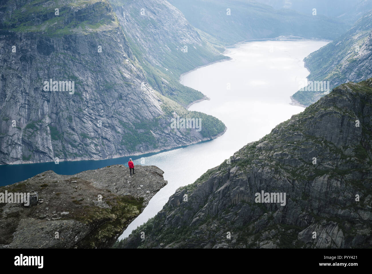 Trolltunga - cliff rock above lake Ringedalsvatnet in Norway. Girl tourist enjoys a beautiful view - Stock Image