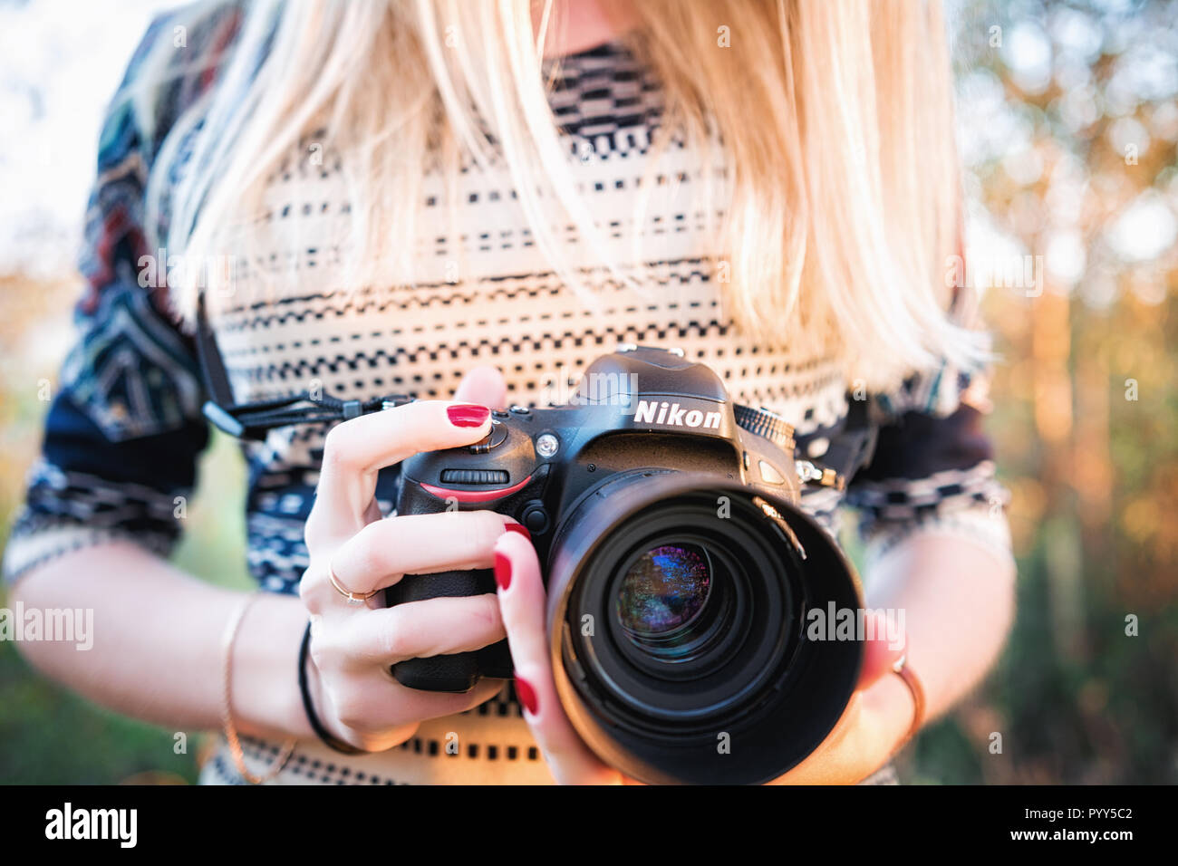 Moscow, Russia - October 4, 2014: Girl photographer holds Nikon D610 camera and Nikkor 50mm f/1.4G lens - Stock Image