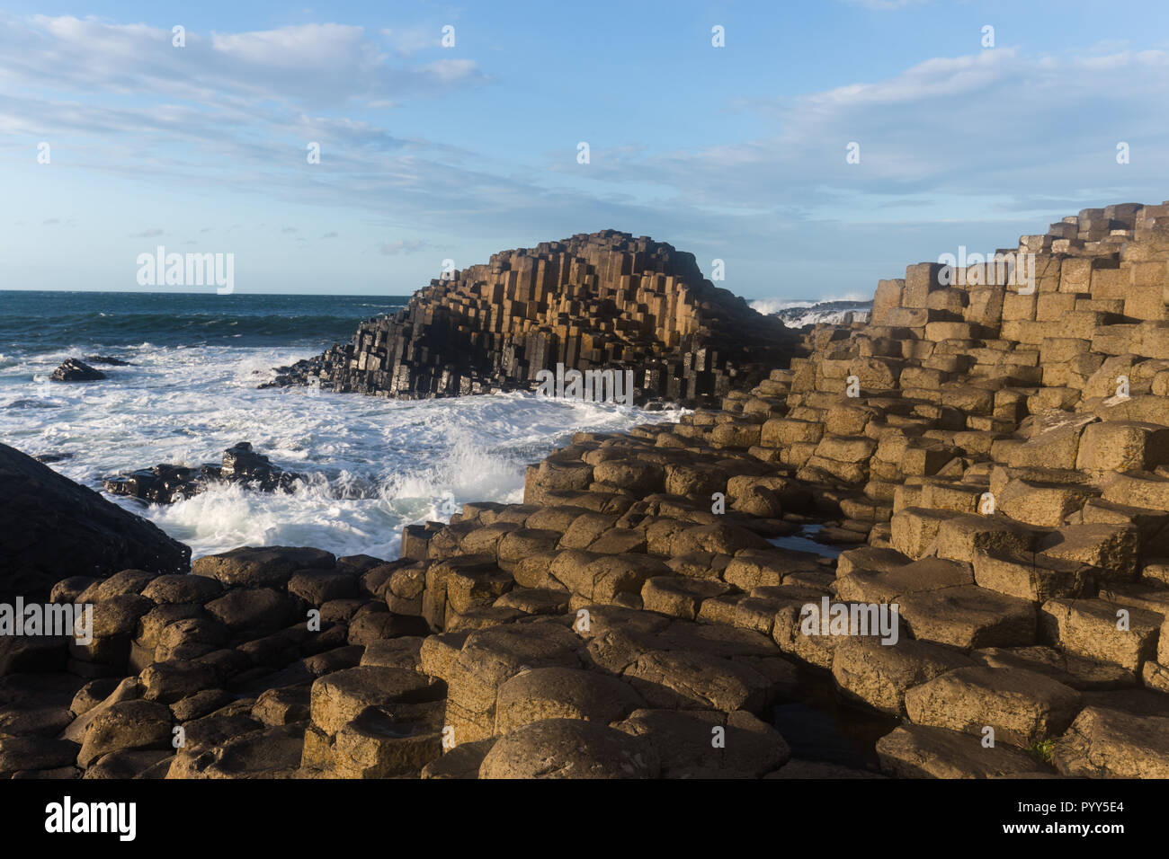 Bright sunny afternoon at Northern Ireland's top attraction, The Giant's Causeway, with thousands of basalt hexagonal columns. Giants Causeway, County - Stock Image