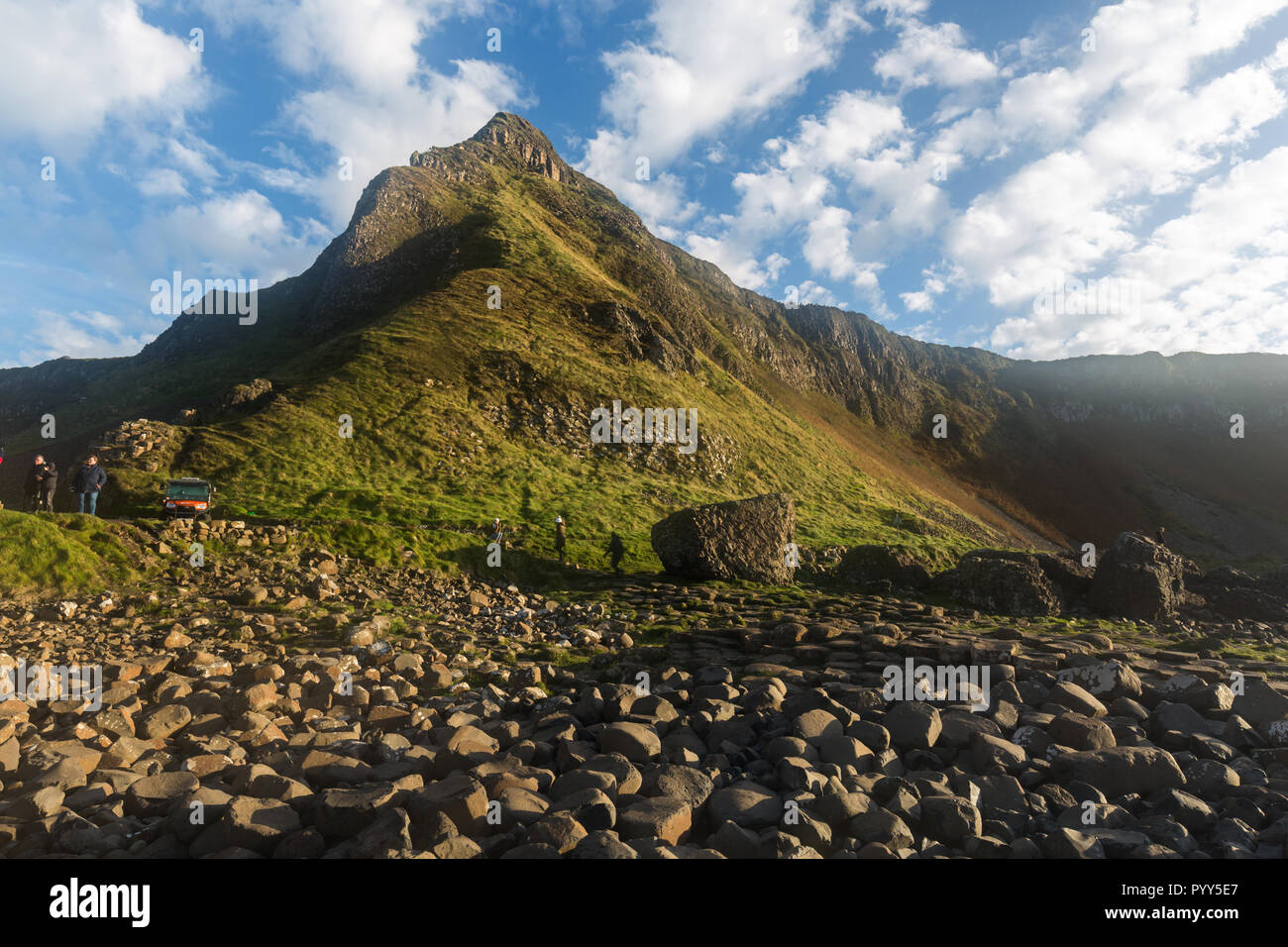 Looking back from the Causeway to the headland behind in bright sunshine with blue skies and white clouds. Giants Causeway, County Antrim, N.Ireland. - Stock Image