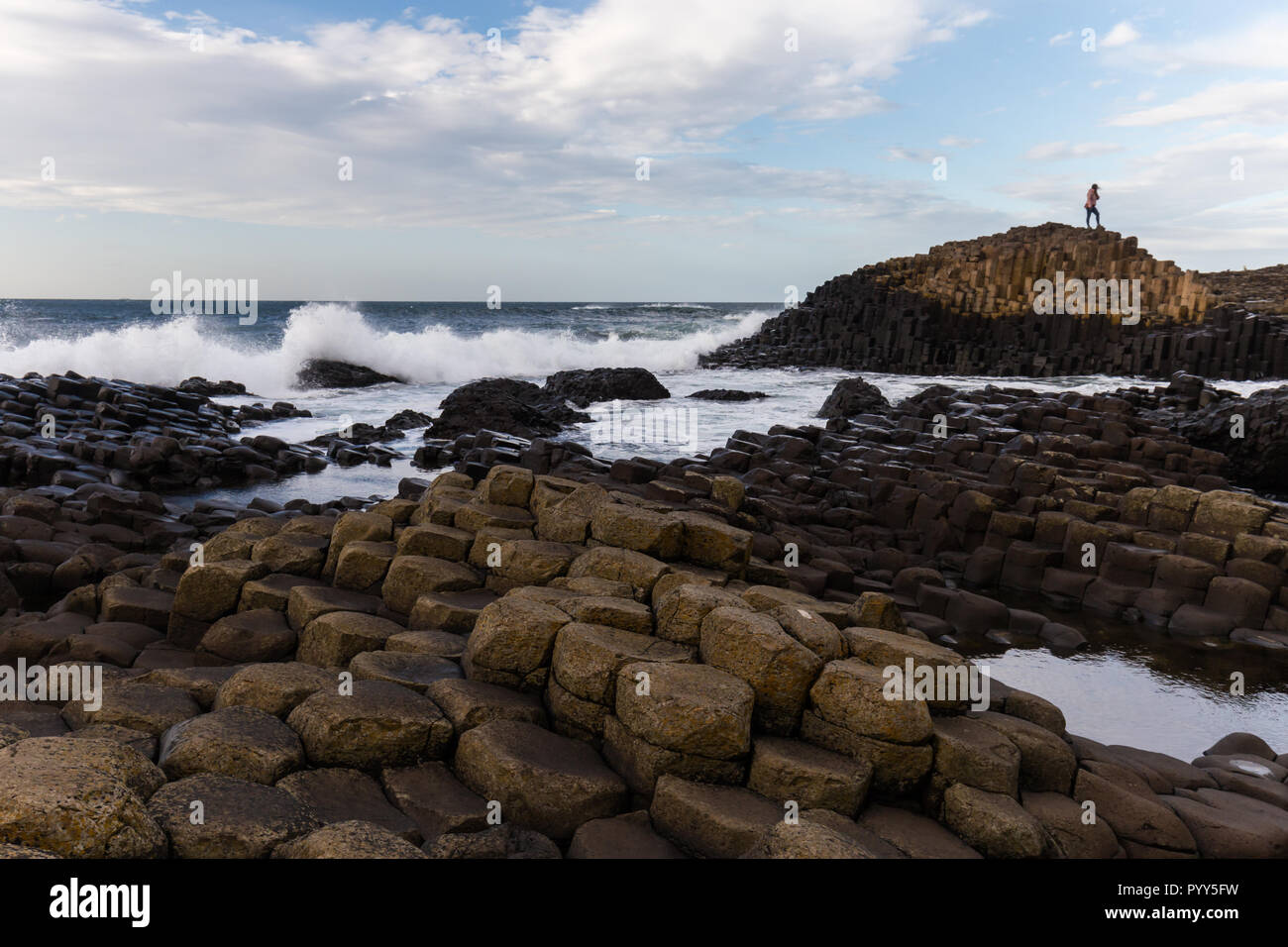 Tourist enjoying a bright sunny afternoon at the top of Northern Ireland's top attraction, The Giant's Causeway, with thousands of basalt hexagonal co - Stock Image