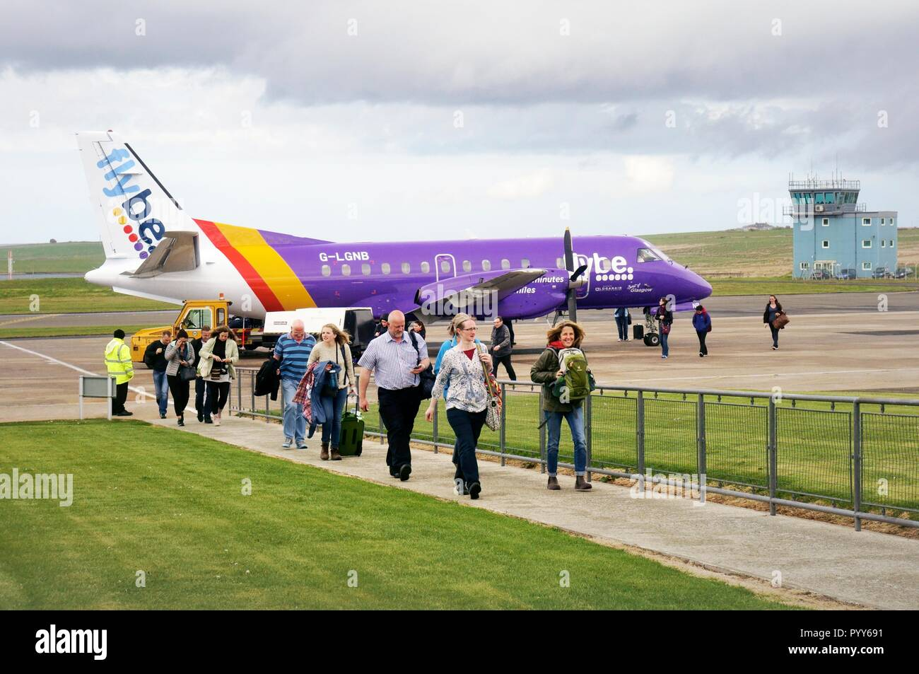 Flybe passenger plane prop aircraft airplane on runway apron passengers arriving at arrival gate at Kirwall Airport, Orkney Islands, Scotland, UK - Stock Image