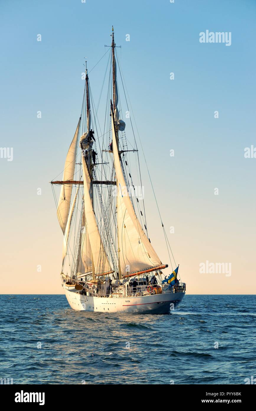 HSwMS Falken. Tall ship training schooner of the Swedish Navy under sail in the Baltic Sea. Crew aloft working sails during course tacking manoeuvre - Stock Image