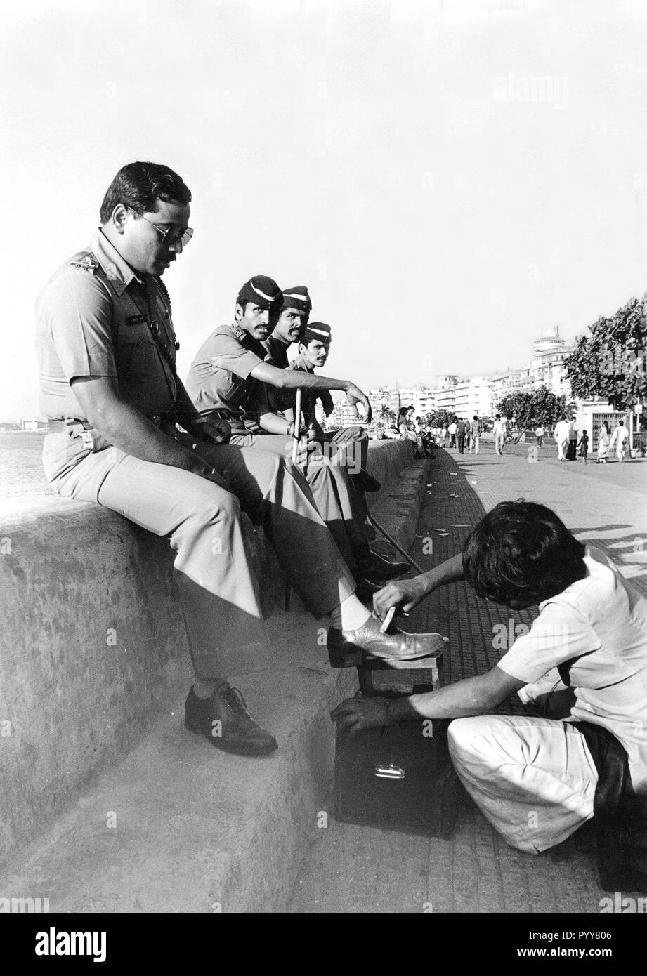 Police officer getting shoe polished, Mumbai, Maharashtra, India, Asia 1900s - Stock Image