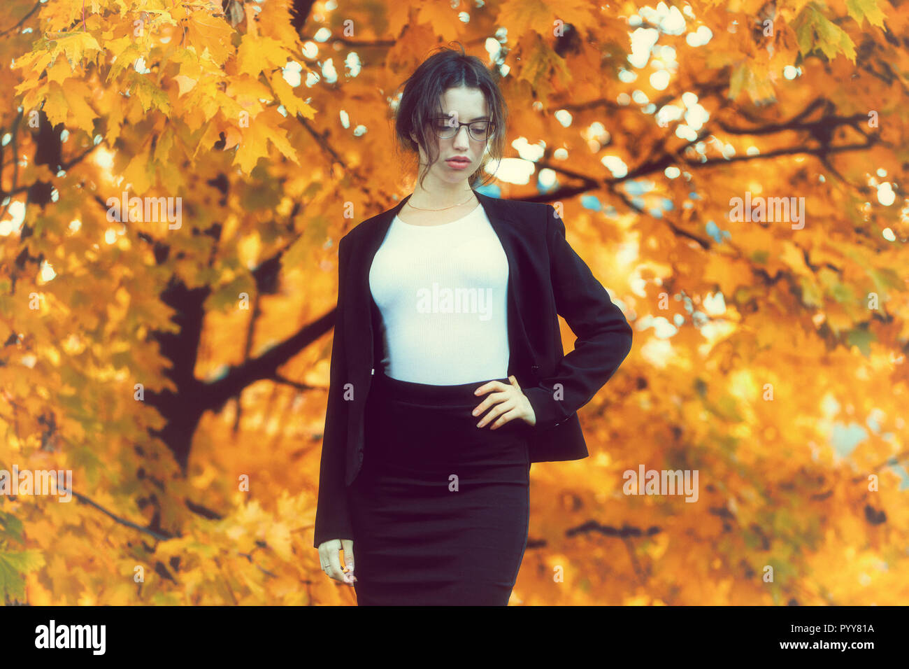 Business woman in formal wear stands over yellow autumn trees. - Stock Image