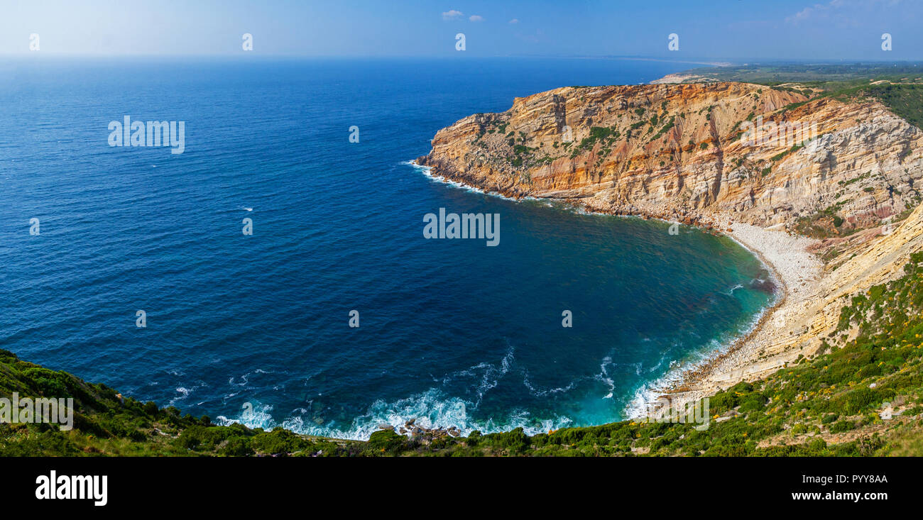 Bay, cove or inlet in Cabo Espichel Cape and a view over the Atlantic Ocean. Seascape of a natural beach surrounded by cliff. Sesimbra, Portugal - Stock Image