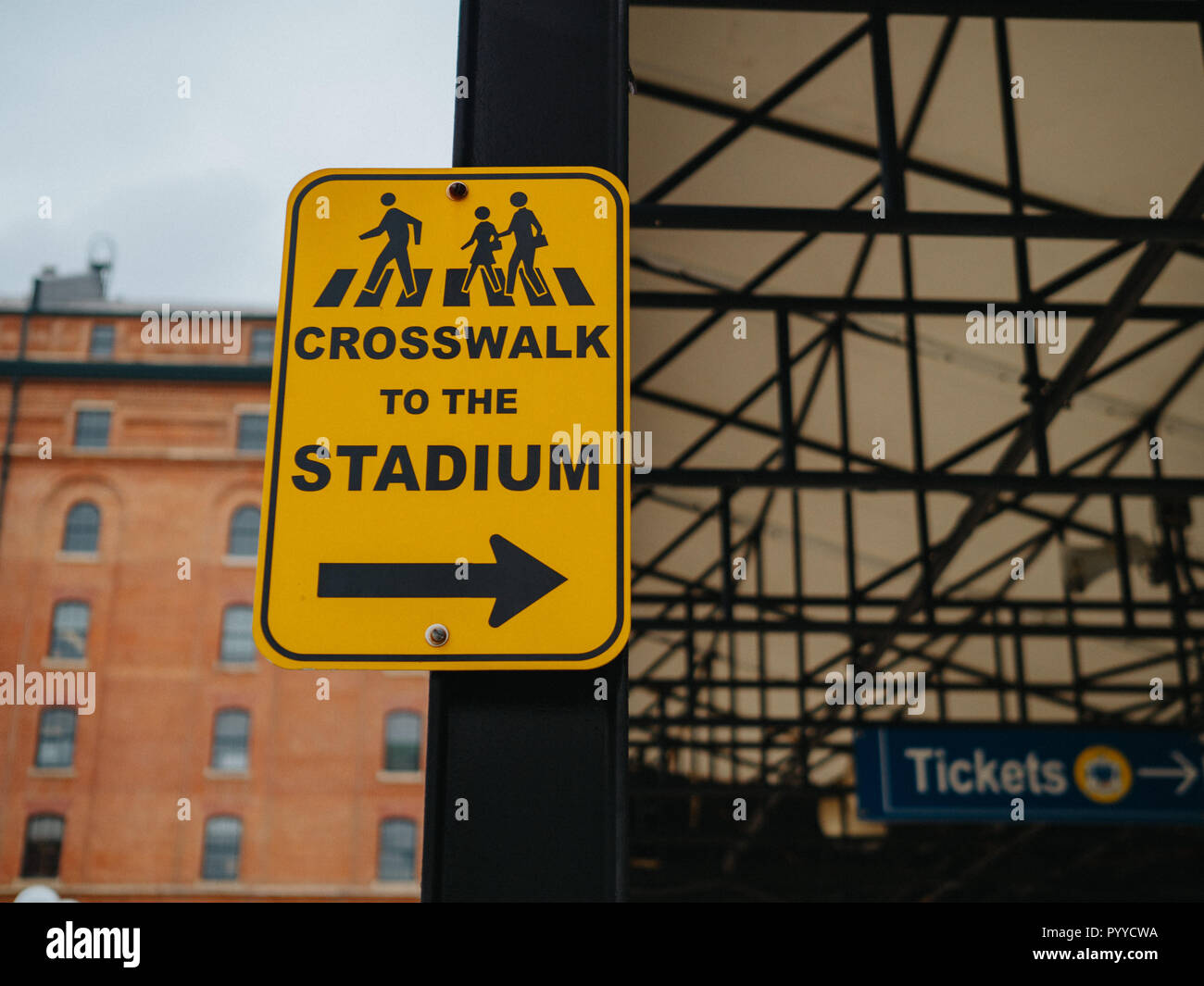 Yellow crosswalk to the stadium sign pointing to the right near a ballpark - Stock Image