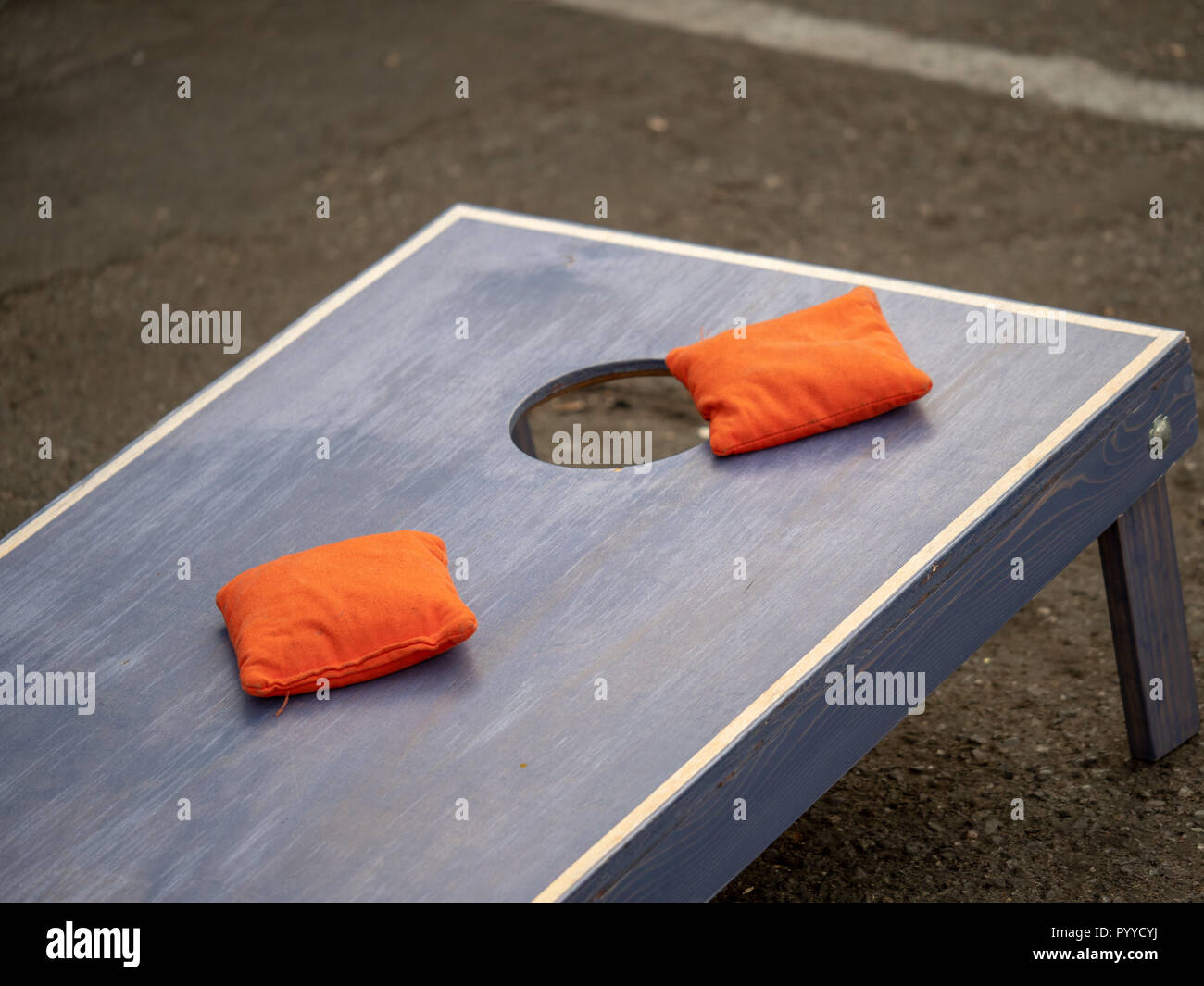Orange beanbags sitting on blue cornhole board platform - Stock Image
